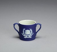 Miniature two-handled mug of white jasper with a dark blue jasper dip, on side one is the arms of the City of Worcester, Worcestershire, England, with a depiction of a turreted castle in the center of a shield and in the upper corner three black pears, surrounding the shield are two crossed branches, one a branch of the black pear tree, the other a palm frond, below the coat-of-arms is a banner with the motto of the City, CIVITAS IN BELLO IN PACE FIDELIS (The City faithful in war and in peace) and the name WORCESTER