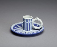 Small chamberstick of dark blue jasper dip with white relief decoration, the saucer with an outer band of overlapping leaves and in the well a circular pattern of stylized acanthus leaves, the candleholder is blue and white striped and has a series of garlands around the neck, the loop handle of white jasper and with a thumbrest in the form of an acanthus leaf.