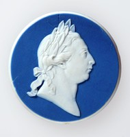 Round dark blue jasper medallion with white relief profile portrait of King George III (1738-1820) facing right. He is shown in profile wearing a laurel wreath like a Roman Emperor. He was married to Queen Charlotte after whom Wedgwood's Queen's ware was so named in her honour.