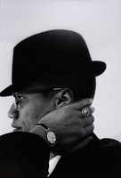 Malcolm X in profile looking left, left hand on side of neck, wearing black hat, watch, and ring.