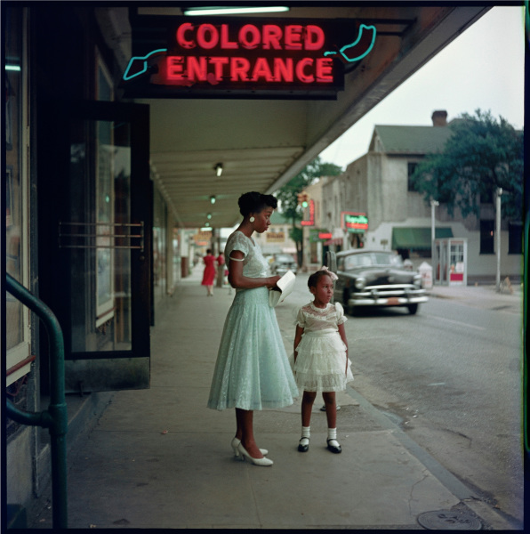 """A black woman and girl in fancy dress, in profile to the camera, stand on the sidewalk outside of a business, probably a store. A neon sign on the overhang above them reads """"Colored Entrance."""""""