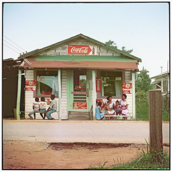 We see, from across a single lane road, a small wooden store that bears signs for Coca Cola, bread and cigarettes. On either side of the screen door entrance, women and children sit relaxing on benches beneath the storefront overhang.