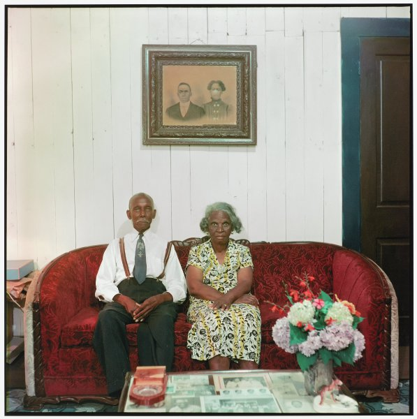 A well-dressed, older black couple sits facing the camera on a burgundy couch.  On the white wall immediately behind them hangs a framed ancestral photograph.  A coffee table in the foreground bears an arrangement of unframed family photographs and a vase of cut flowers.