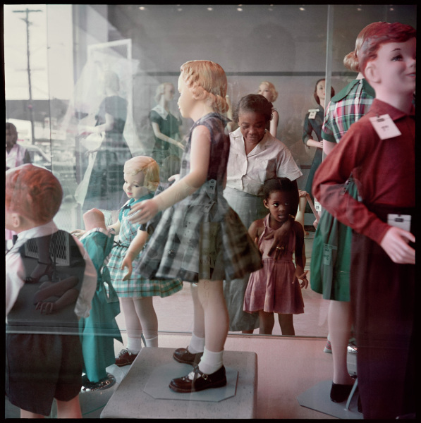 A black woman and girl stand within a store entryway, facing a display window filled with white child mannequins. The girl is looking and pointing at the display, while the woman, her arm around the girl, is looking downward.