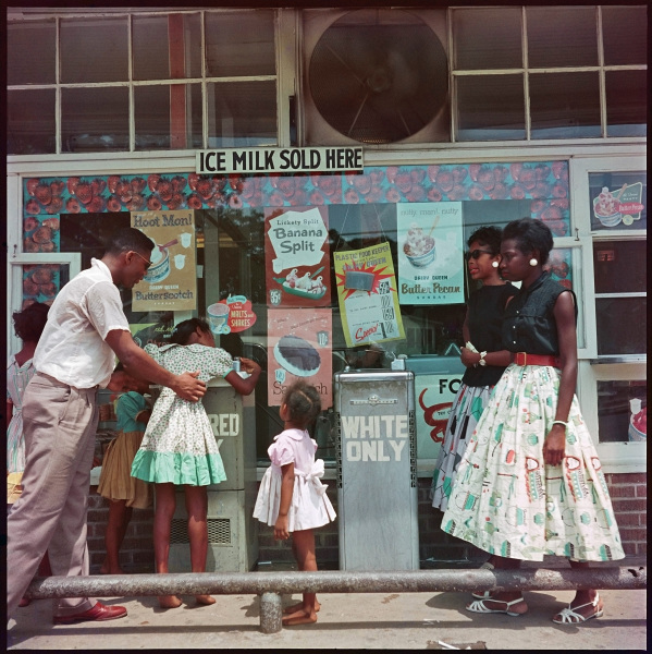 """A man, two identically dressed women, and four girls, all black, are gathered outside of an ice cream parlor. The man is helping one of the girls reach to drink from a """"Colored Only"""" drinking fountain. A """"White Only"""" fountain stands beside it."""