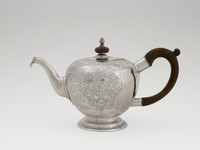"""Silver teapot of bulbous form on a stepped circular foot and with an S-shape spout, engraved on one side of the body with the arms of the Gardiner family, a branch of the Gardiner's Island, NY Gardiners in Boston, the opposite side with the pricked date """"1746,"""" which is not contemporary to the piece, the shoulder and hinged lid engraved with Rococo scroll- and lattice work, topped by a wood knop finial with silver pinecone bud, and with loop handle of fruitwood."""