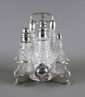 Assembled cruet set comprised of a silver frame and five mounted, cut-glass bottles, the cinquefoil base resting on four cast shell feet attached to cast double C-scroll stretchers, the stretchers extend from the rim of the base to five circular guard rings, on one side with an applied foliate, floral and shell cartouche engraved with a coat-of-arms (illegible), the handle is attached to a baluster stem, the five cut glass bottles of varying sizes with silver covers each decorated with engraved geometric motifs.
