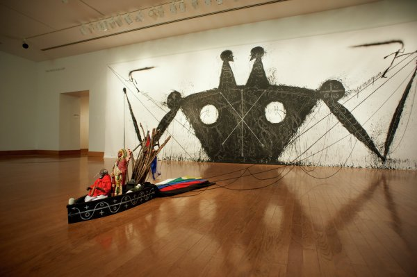 """A large-scale installation work comprising an un-stretched canvas painting, metal chains, and various three-dimensional elements.Layout- A small boat/vessel sits on the floor 12 feet 8 inches out from the wall.  Four pairs of slender black metal chains attached to its stern connect the vessel to four points on a large rectangular canvas on the wall behind it. (The chains attach to black screws that pierce the canvas and anchor into the wall behind it.) The outer pair of chains are 19 inches 4 inches long when taut; the inner chains are approximately 15 feet 10 inches when taut. Each pair of chains comprises a taut strand and a lower strand suspended below the taut strand in four arcs.Vessel- Black wooden vessel with hand-drawn white conté motifs of arrows and circles on each side. Three inner partitions, each with its own contents. The rear section holds a black metal cauldron, roughly seven inches in diameter. Inside the cauldron is an assortment of roughly twenty sticks, a dark grey stone acting as a counterweight to the sticks, and a miniature Cuban flag. In the middle section stands a 20 inch tall Native American Chief figurine alongside a bottle of rum with a label that reads """"Aguardiente de caña / OGGÚN / 100 Proof."""" In the front section of the vessel is a 13 inch tall male figurine of African descent, clothed in a red and white satin robe, seated in a figurine chair with a partially burnt (actual) cigar near one hand. At the stern of the vessel, 6 strips of colored fabric overlap and trail behind, in order from left to right when viewed from the front:white, yellow, green, blue, red, blackCanvas- Large pictorial image of two figures conjoined by a large torso, with two arms, two necks and two heads looking at the other. Largely two-dimensional with few references to perspective. Dense black acrylic with hand-applied patterns and white conté accents of arrows forming an X with a central vertical arrow. Canvas splattered plentifully with black acrylic, extendin"""