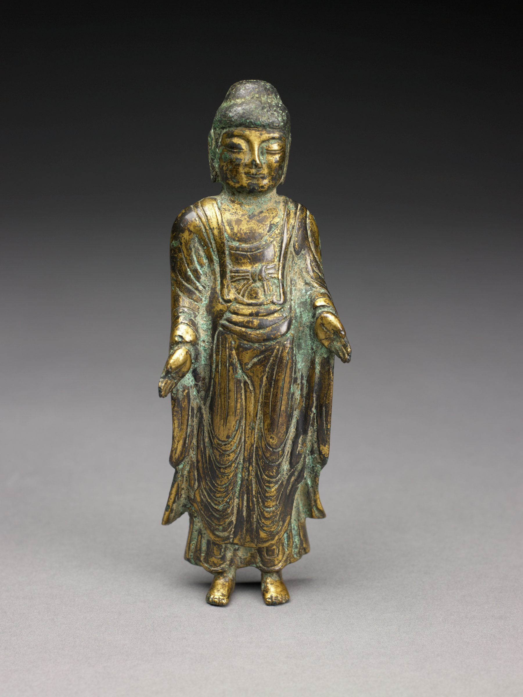 Standing image of Buddha, base missing, two long tangs in feet. Back is hollowed with protruding flue(?) or tenon in upper chest. some oxidization