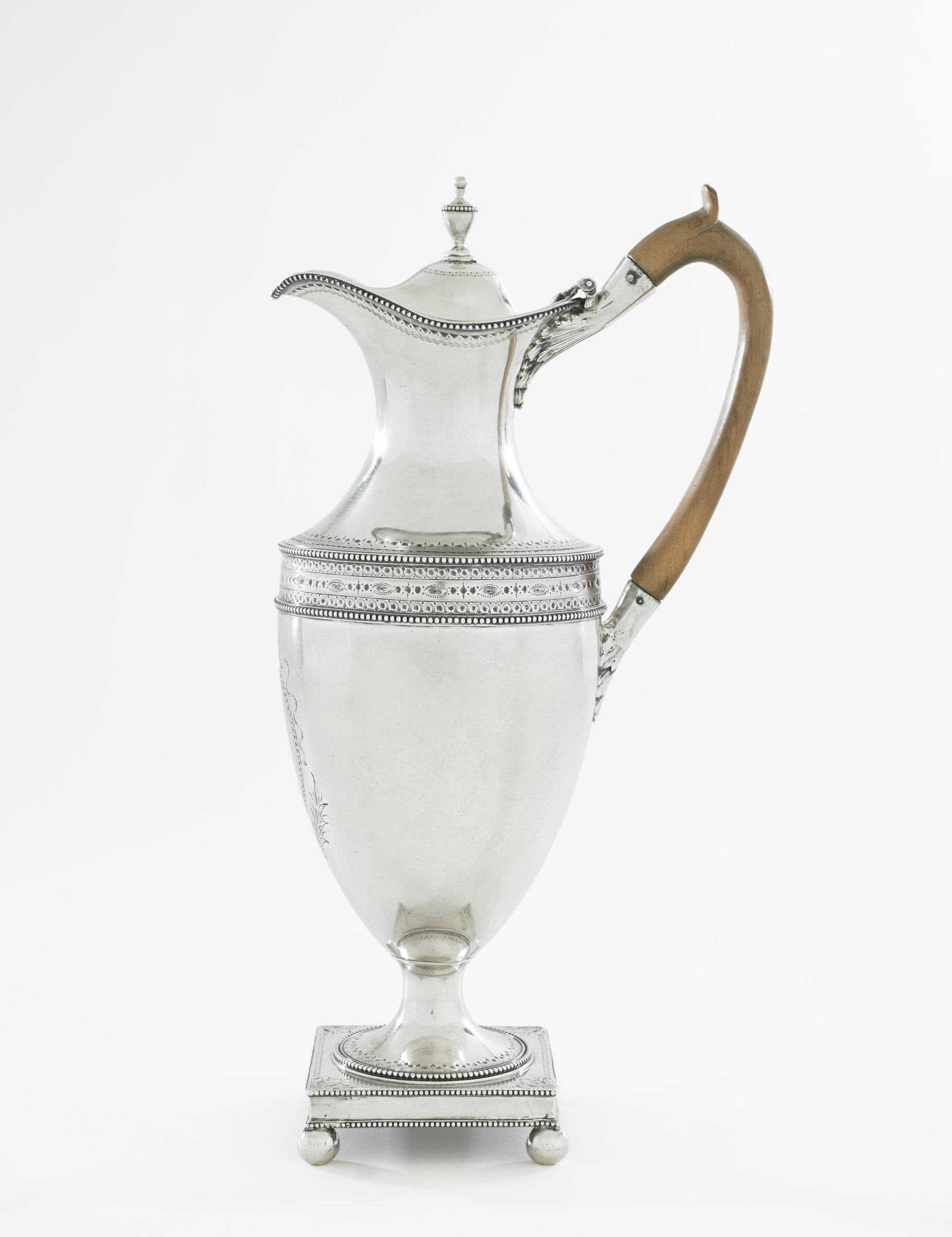 Silver hot water jug resting on short stem that tapers to small, round beaded foot accented with bright-cut engraving in a scallops and dot pattern, resting on a square plinth with four ball feet, the plinth decorated with bright-cut engraving comprised of floral elements at each corner with dots in between, the urn-shaped body with a wide band of engraved ovals and dots at the shoulder between an upper and lower band of beading, the neck narrows in the middle, the lower edge likewise engraved with a decorative pattern, the beak-shaped spout edged with beading, the hinged lid with urn finial, with attached ear-shaped walnut handle with thumb rest, the main body under the spout engraved with an oval reserve with crossed leafy branches and a ribbon (left empty).