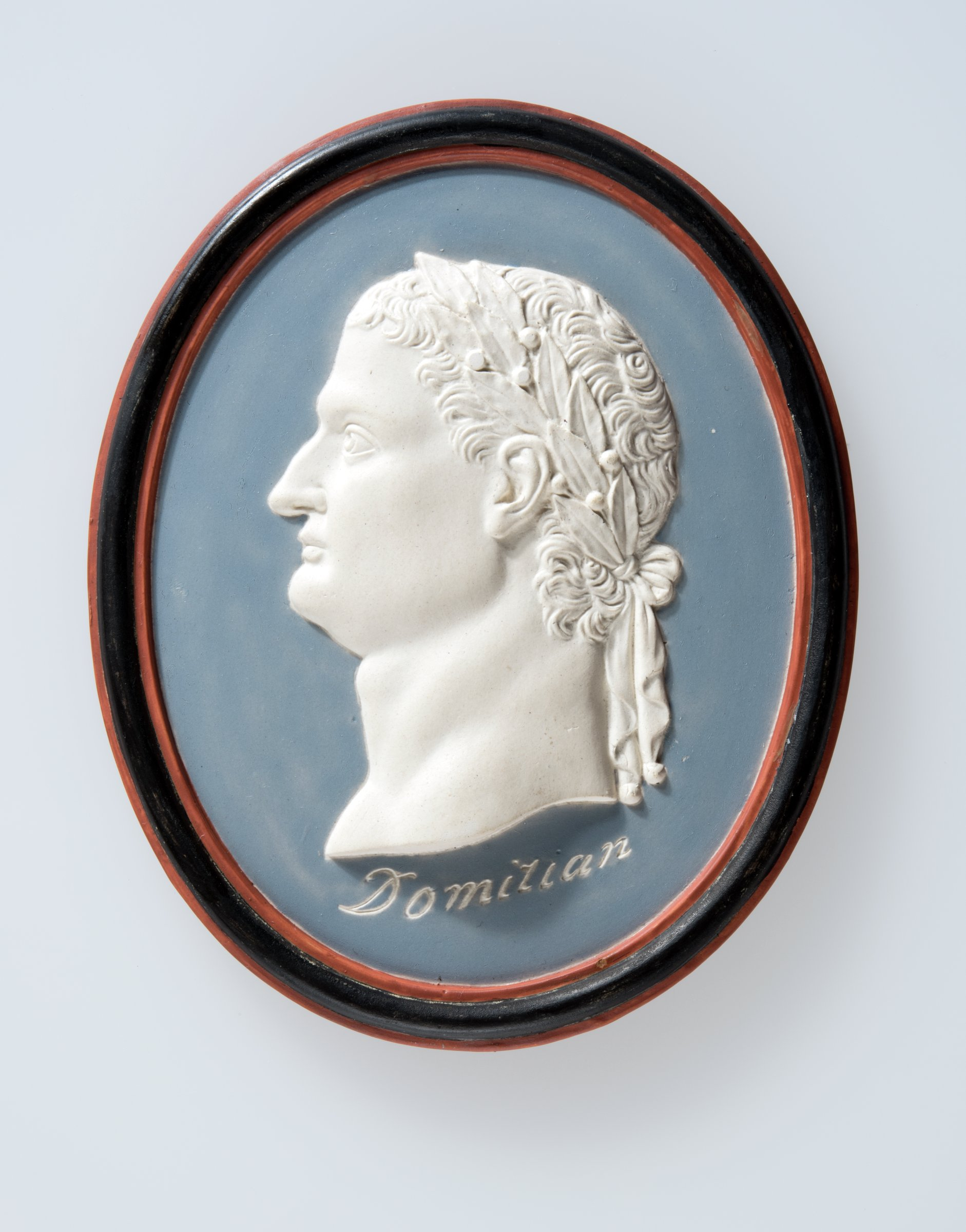"""Oval medallion of enameled creamware with the portrait of the Roman Emperor Domitian with laurel leaf crown to left and the name """"Domitian"""" below the truncation, the portrait is cream while the ground is a light blue with a border of Etruscan red and black, the reverse likewise enameled light blue."""