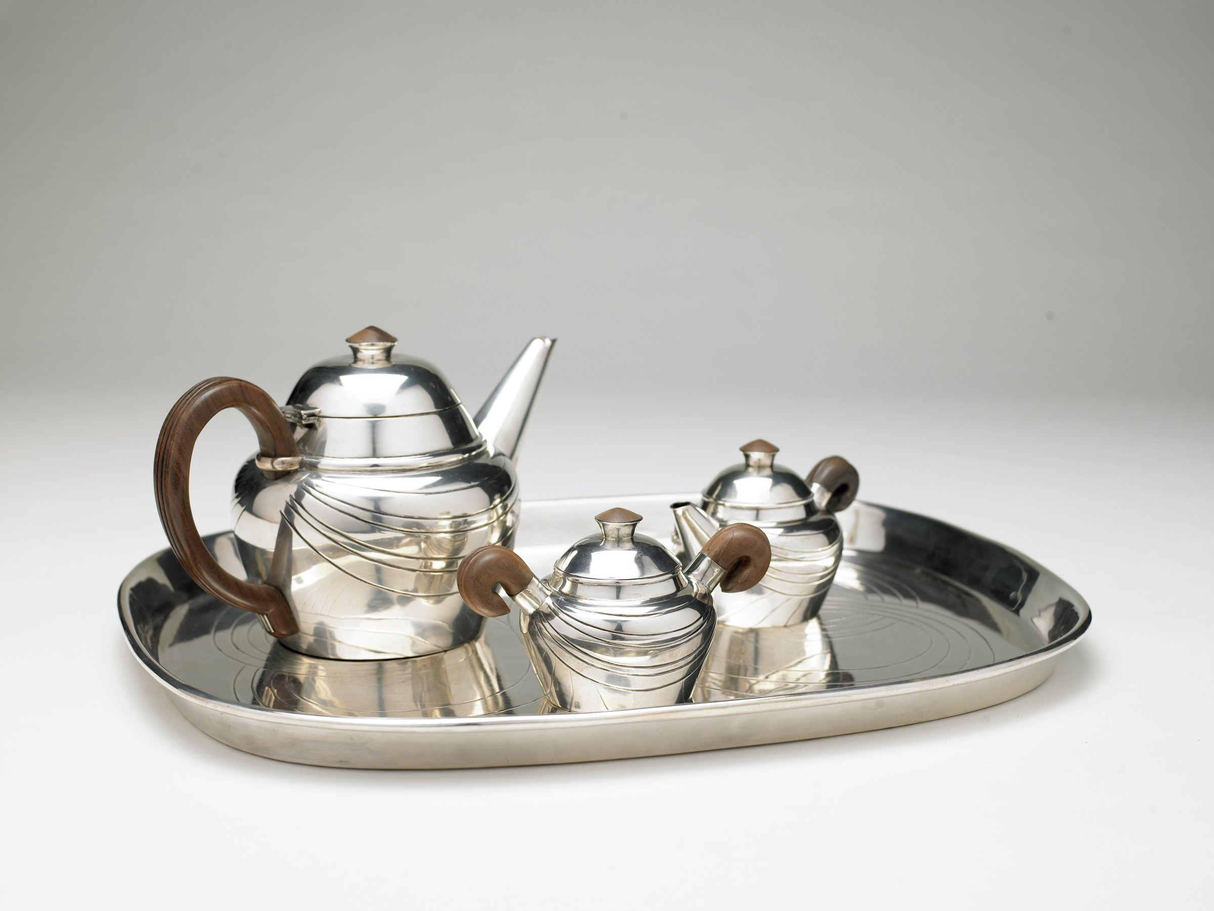 Four piece part tea service consisting of lidded teapot, covered sugar and covered creamer with matching tea tray, all pieces of baluster form with domed covers and rosewood handles and finials, engraved with stylized swags, the rectangular tray with raised rim engraved with interlaced strapwork.