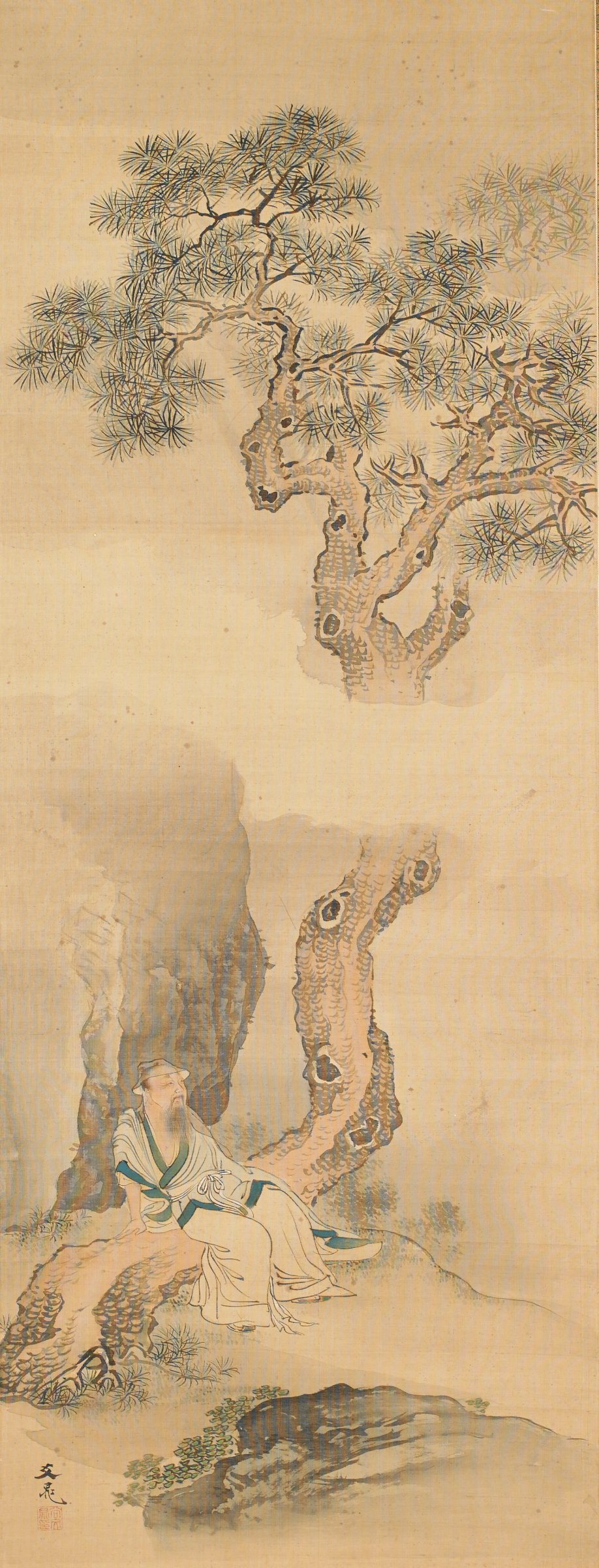 Figure sitting on a pine tree with a hat used to strain tea.