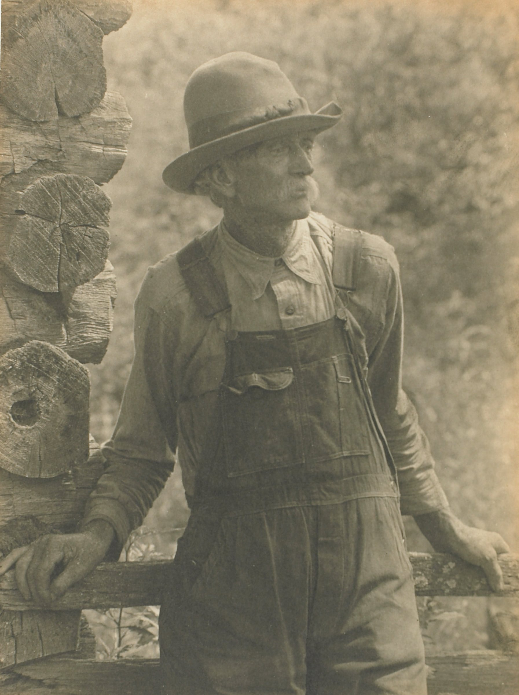 A black and white portrait of an unknown man dressed in a button-down shirt and overalls. The man leans against a wooden rail attached to the edge of a log-cabin.