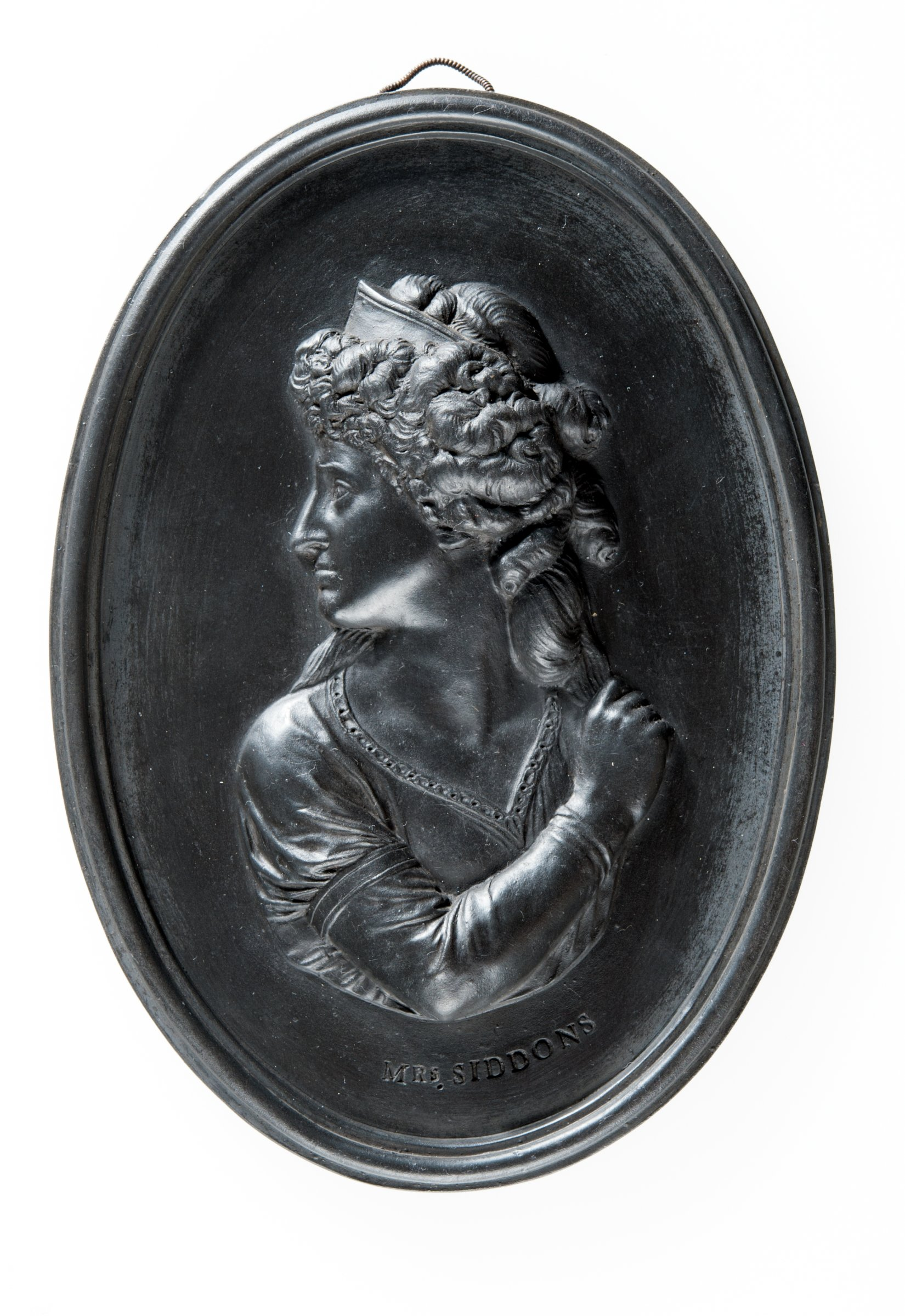 Oval basalt medallion with profile portrait of Mrs. Sarah Siddons (1755-1831) facing left. An English actress who was born in Brecon, she married the actor William Siddon in 1773. She was engaged by David Garrick to play at Drury Lane.
