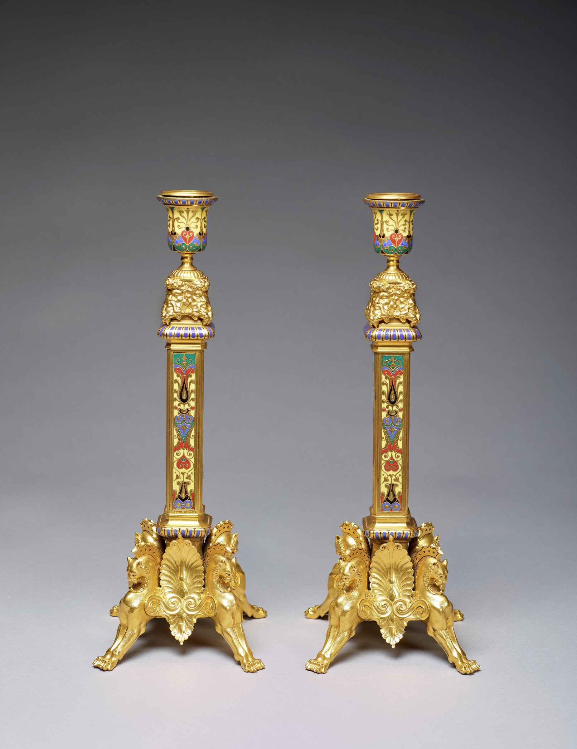 Pair of tall, gilt-bronze candlesticks in the Neo-Byzantine style, each resting on four regal-looking, stylized winged panthers, with square columnar stems decorated with brightly-colored enamel in the cloisonné technique in a pattern of scrolls and leaf motifs, the top and base of the stem with gadrooning highlighted in blue enamel, with four bearded masks at the top of the stem supporting an urn shaped candle nozzle that is likewise decorated with bright enamel in the cloisonné technique and with a band of gadrooning highlighted in blue at the upper edge.