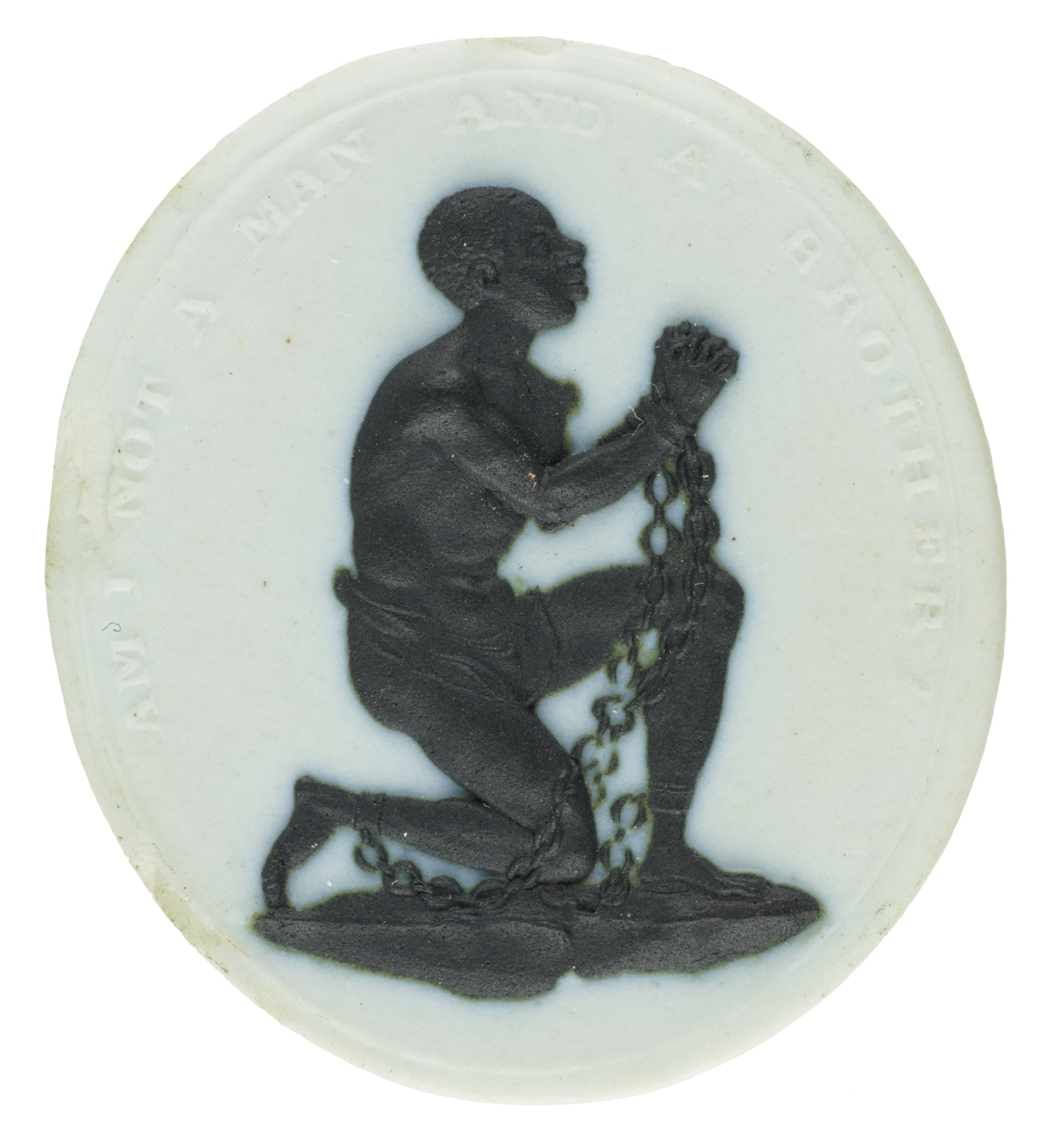 Small oval medallion of white jasperware with black jasper relief of an African slave wearing only a loin cloth, kneeling and in shackles, with his hands grasped together, around him the inscription AM I NOT A MAN AND A BROTHER?