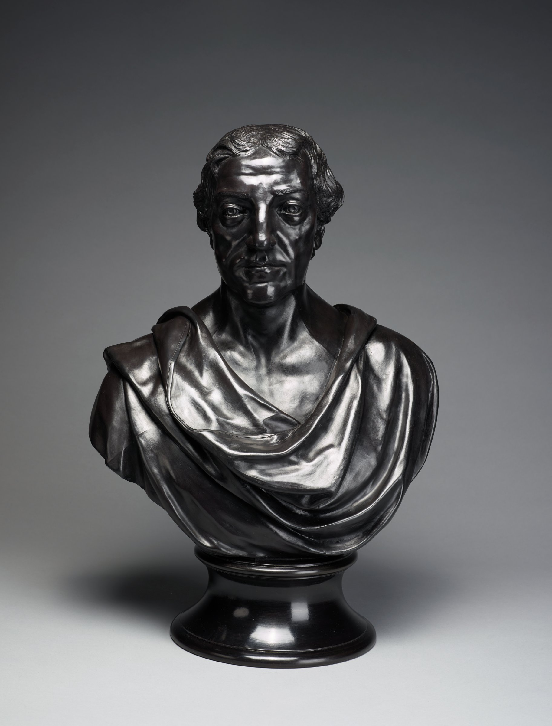Portrait bust in black basalt of William Pitt, 1st Earl of Chatham in classical drapery on round socle (probably not original).