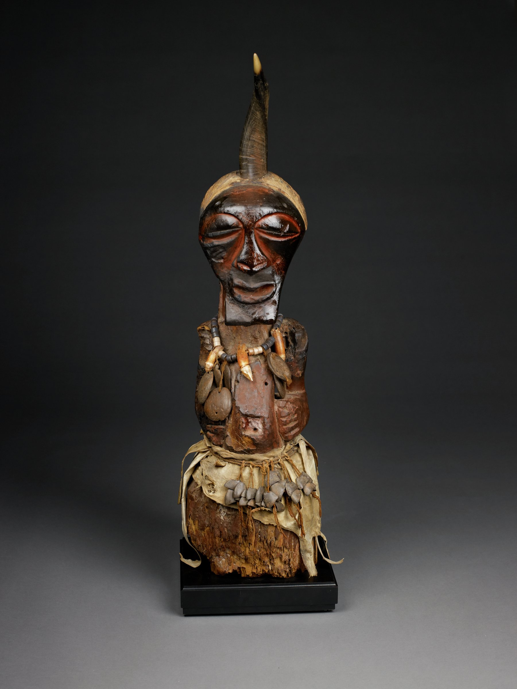 Standing male power figure with bent arms resting on distended abdomen; below abdomen, figure is unarticulated block, partially covered by animal skin and waist ornaments (large bell and metal jangles attached to cord). Animal horn emerges vertically from top of head. Face has slitted, bulbous eyes, broad nose, protruding and slightly upturned open mouth, square beard. Necklace of glass beads, animal teeth, seed pods hangs from neck onto abdomen. Umbilical area has opening where medicinal materials once existed.