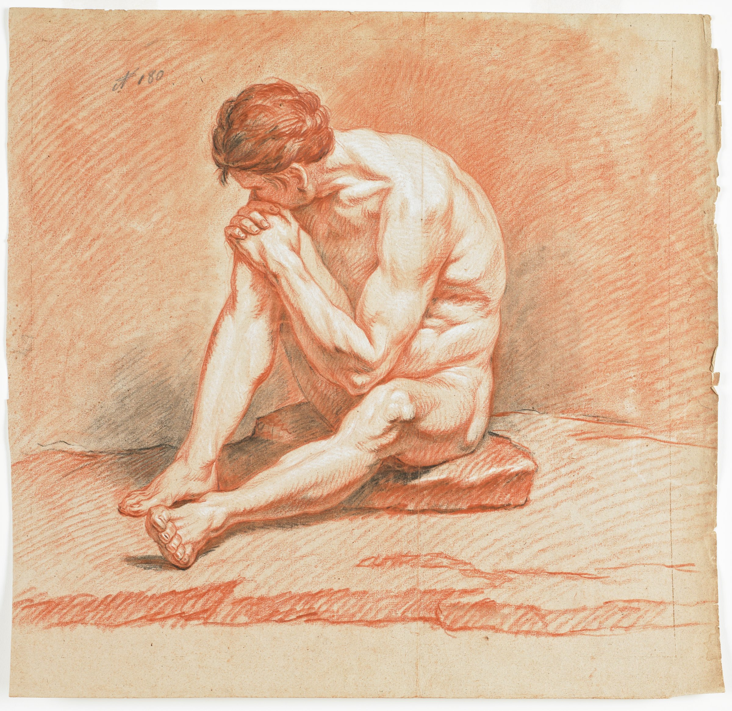 Nude man seated on a stone with left leg bent and right knee pulled up, with hands clasped over knee. Left cheek resting on hands with head turned away from viewer.