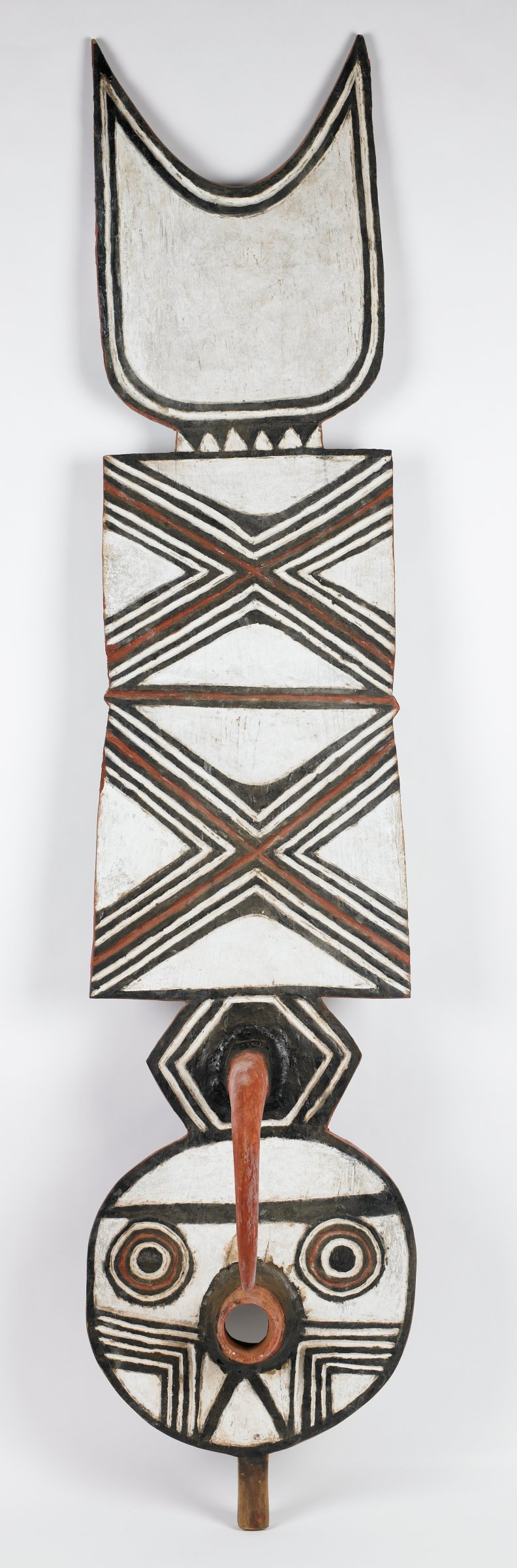"""Tall vertical plank surmounts circular """"face."""" Patterns on plank are carved and painted with red, black, and white pigment. Patterns on front include two large """"X"""" designs, one atop the other. Top of plank is sculpted into upturned crescent moon shape. Back of plank has checkerboard pattern. Hood """"beak"""" shape extends from front of circular face, pointing downward toward circular """"mouth"""" opening. Deep oval shape extends from back side of face to cover masquerader's face. Holes around edge of oval for rope to secure mask to back of masquerader's head."""