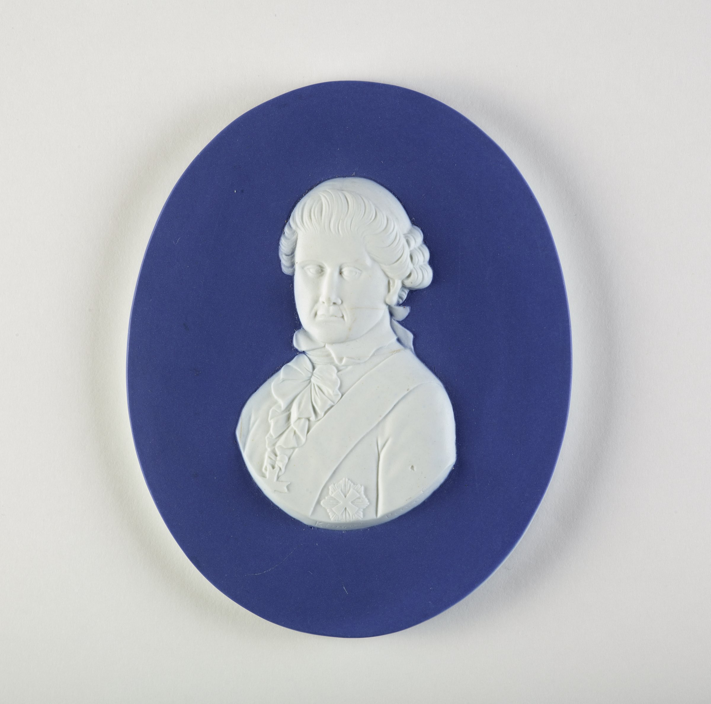 Oval portrait medallion of white jasper laminated between two surfaces of dark blue jasper dip, the portrait of the King of Portugal in civilian dress with sash to front in white relief.