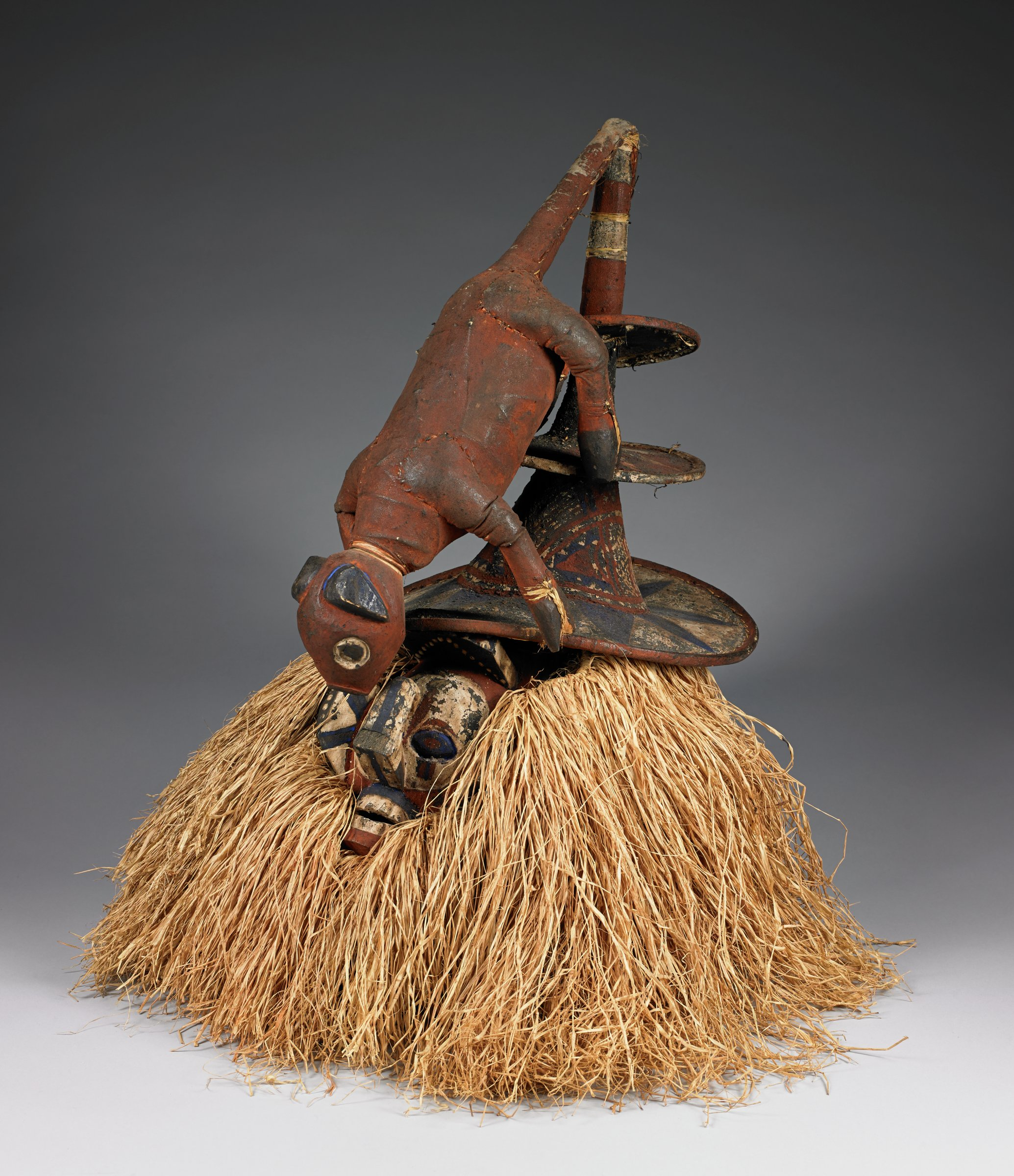 Helmet mask with carved and painted pig attached to hat