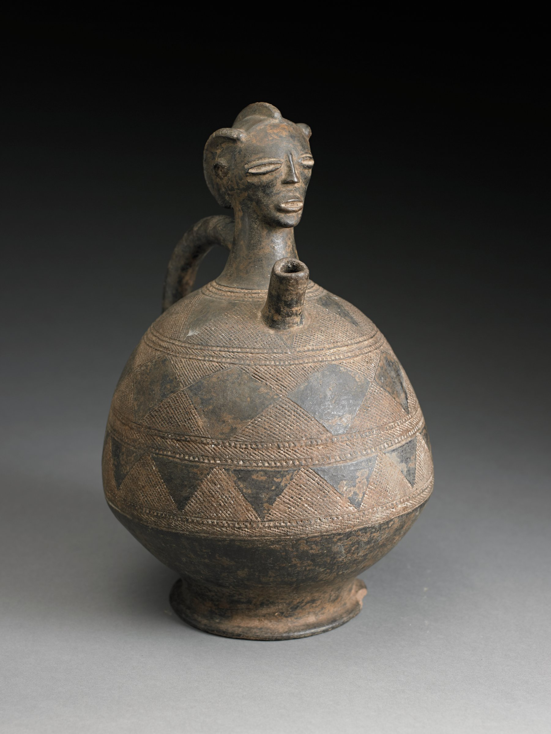 Vessel topped with female head has narrow, cylindrical spout and strap handle. Head has three rows of plaits, closed coffee-bean eyes, nose and mouth.  Body and shoulder of vessel have three registers of decoration, consisting of alternating triangles and diamonds.