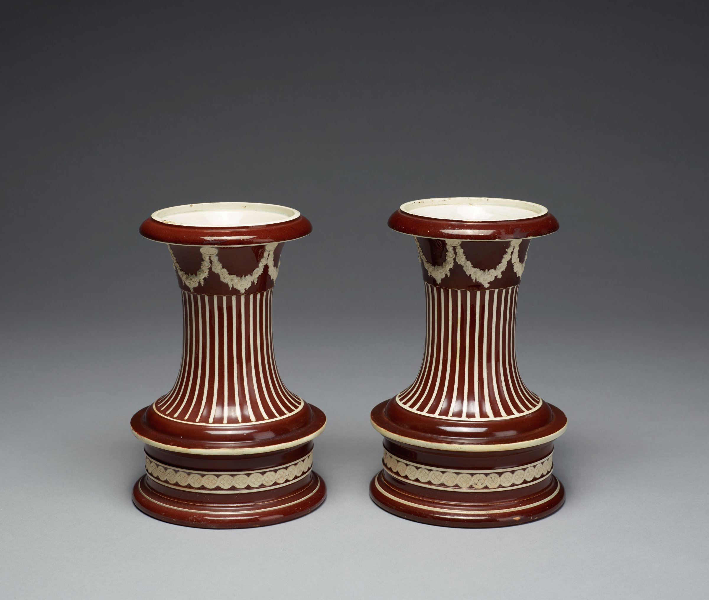 Pair of vases of pearl-glazed, white stoneware covered with a brown glaze and engine turned to reveal the white stoneware below the glaze, baluster shaped with fluting on the stem highlighted in white, with a row of applied white floral garlands suspended by medallions below the flared lip and an applied white band of repeating medallion motifs around the base, the covers are missing.