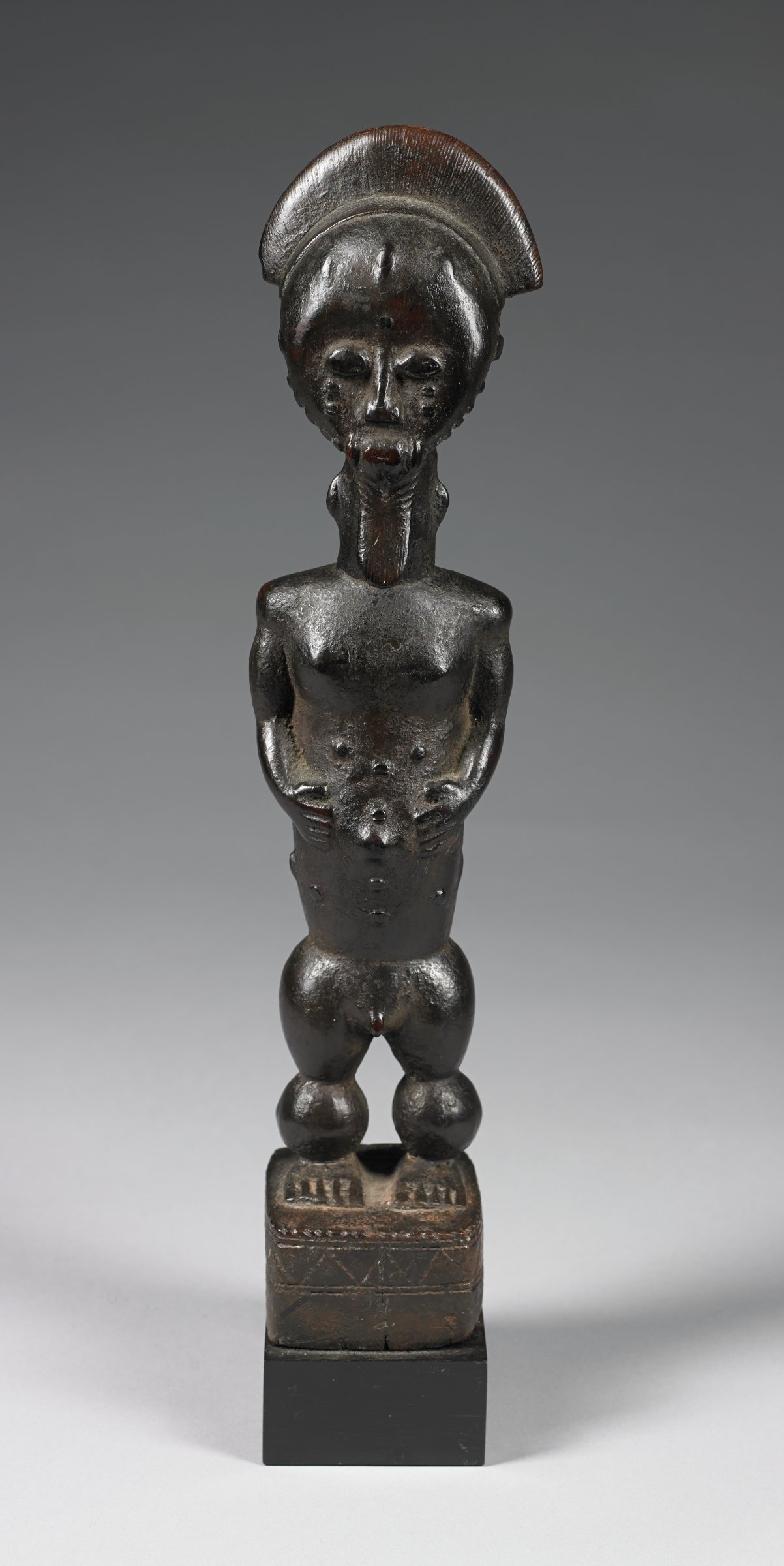 Male figure with pointed beard, crested coiffure, body scarification, short legs with exagerated musculature, with overall worn patina.