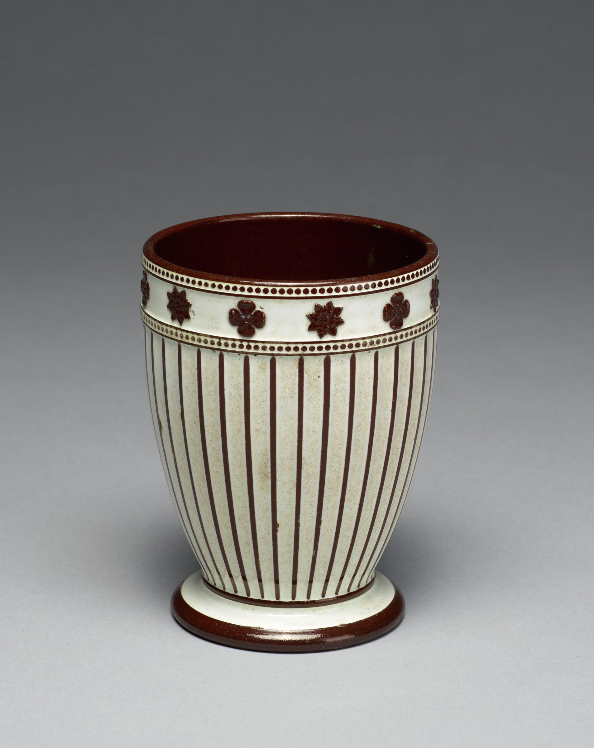 Small cup-shaped vase with foot, of white stoneware covered with a brown glaze, the main body fluted and decorated with a series of cream and brown stripes, below the lip a band of cream with applied brown star-shaped and clover motifs between two rows of beading, the interior glazed brown.