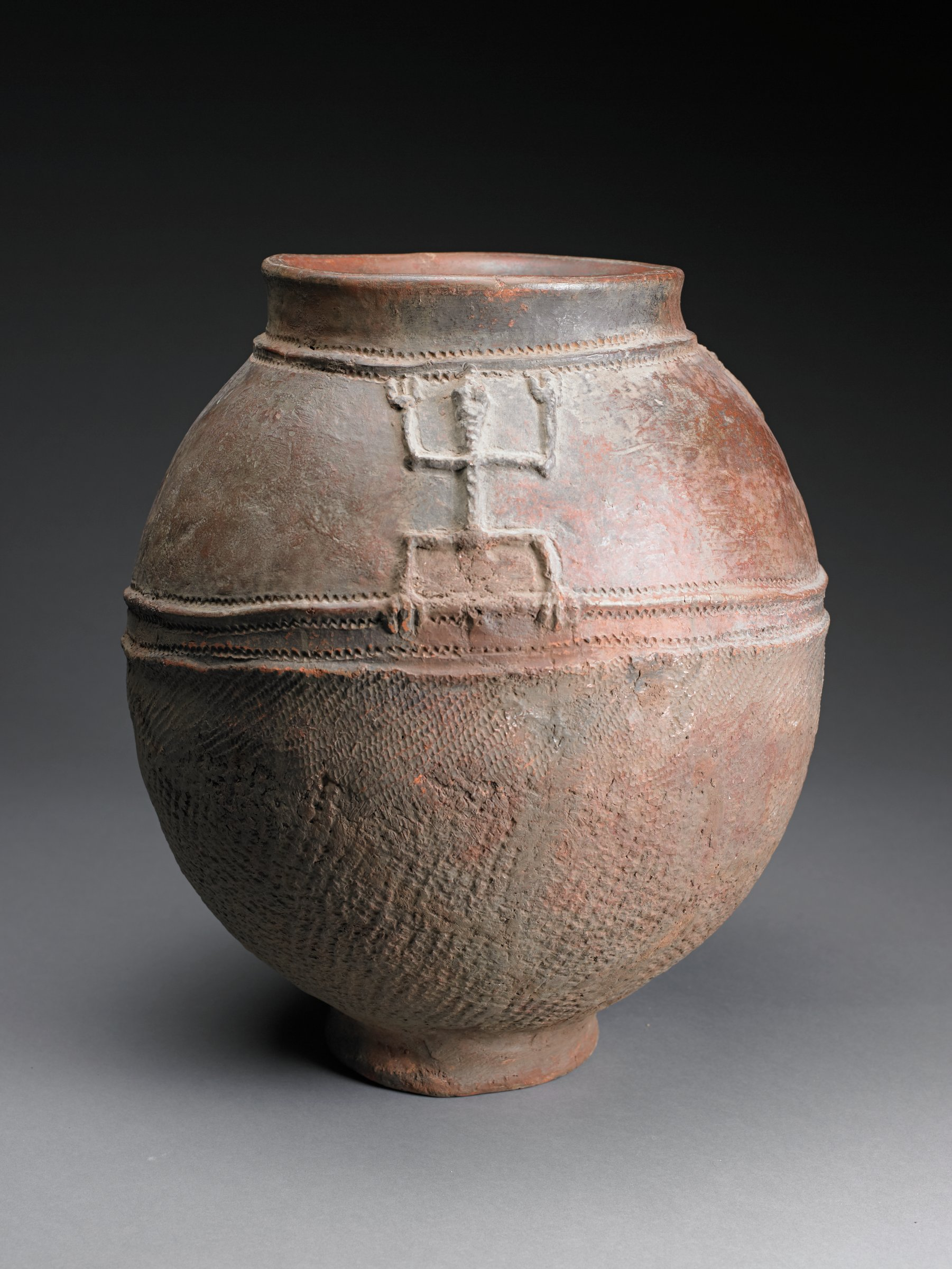 Brown ovoid jar with narrow, short foot and short rim. Shoulder has geometric lizard forms; raised ridges with zig-zag lines at at top of shoulder and mid-point of body. Bottom half of vessel has patterns from impressed cord.