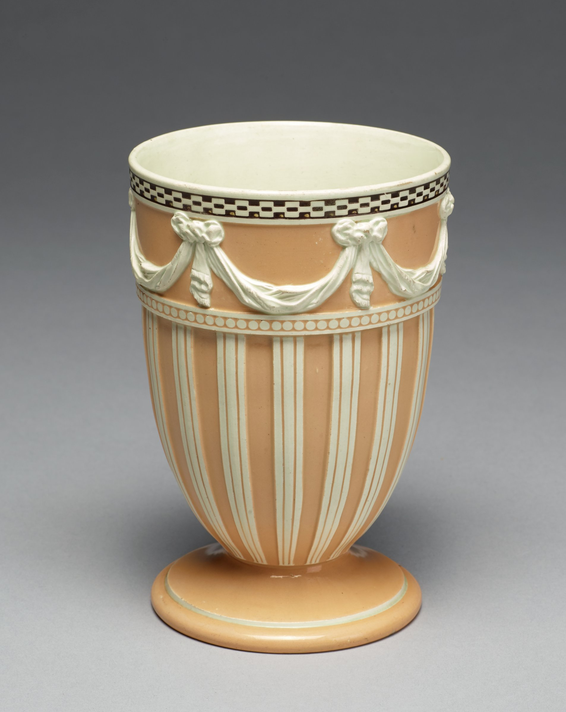 Vase of goblet shape on round foot, of white stoneware covered with a yellow glaze, the main body with yellow and white stripes, above a band of beading and against a yellow ground a band of molded swags, immediately below the lip a band of black and white checkerboard pattern, the interior white.