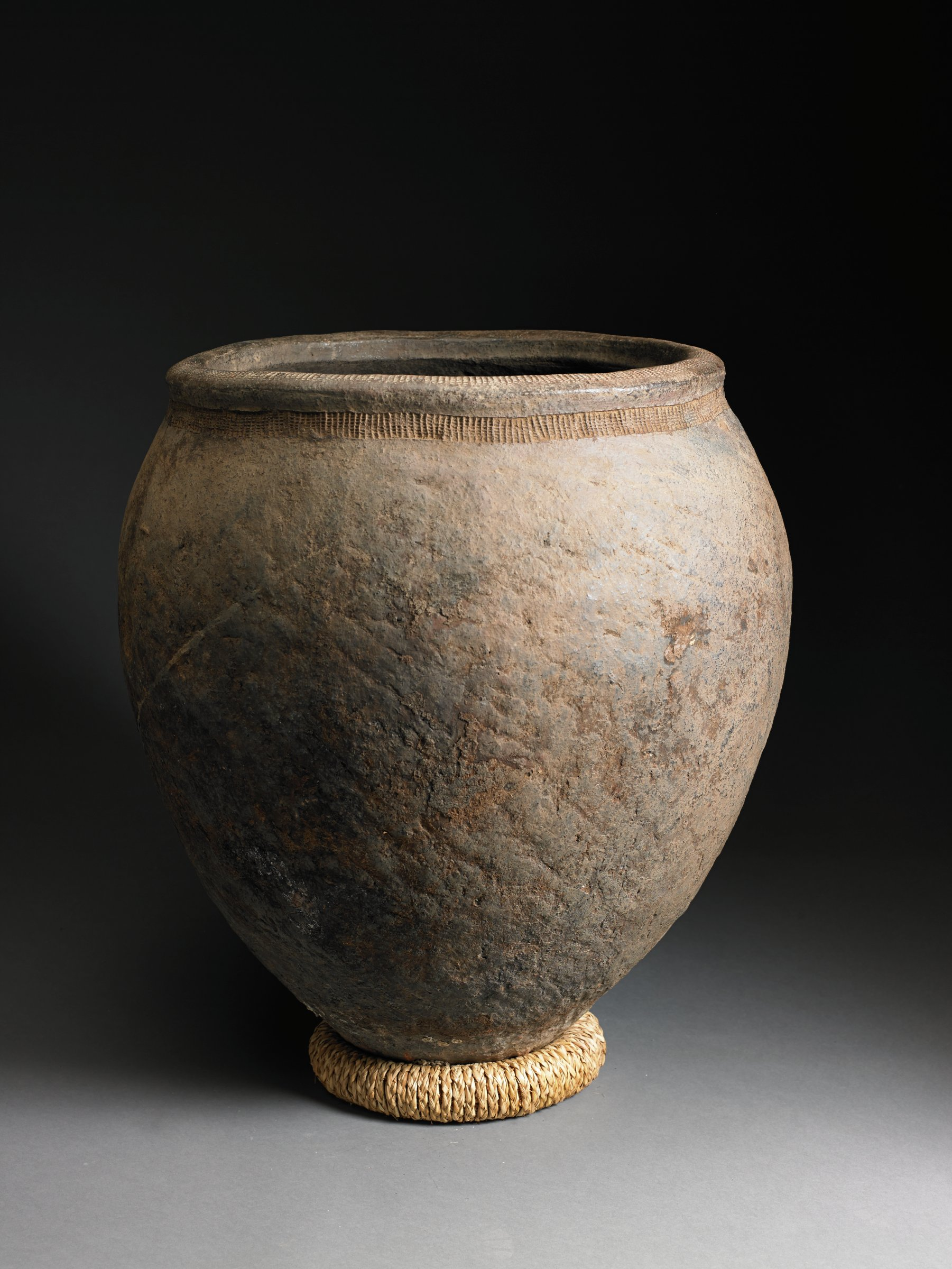 Ovoid brown jar with wide mouth and short flared lip tapers to narrow bottom. Jar has variegated color and overall surface texture with narrow checkerboard band just under lip.