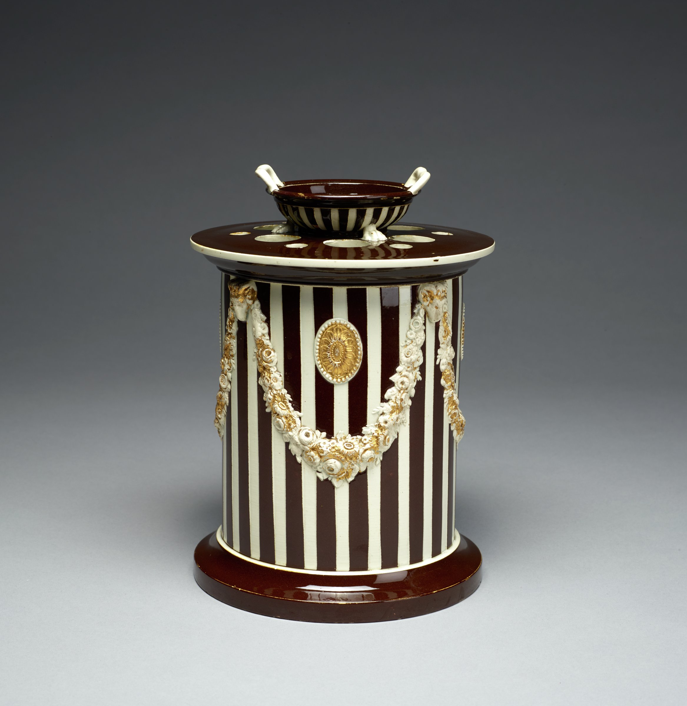 Censer, or incense burner, of white stoneware covered with brown glaze under a clear pearl glaze, drum shaped with a series of vertical white stripes around the body and gilt floral garlands held by rams' heads with gilt paterae between, with flat perforated cover with a central opening in the form of a two-handled bowl, likewise with vertical white stripes.