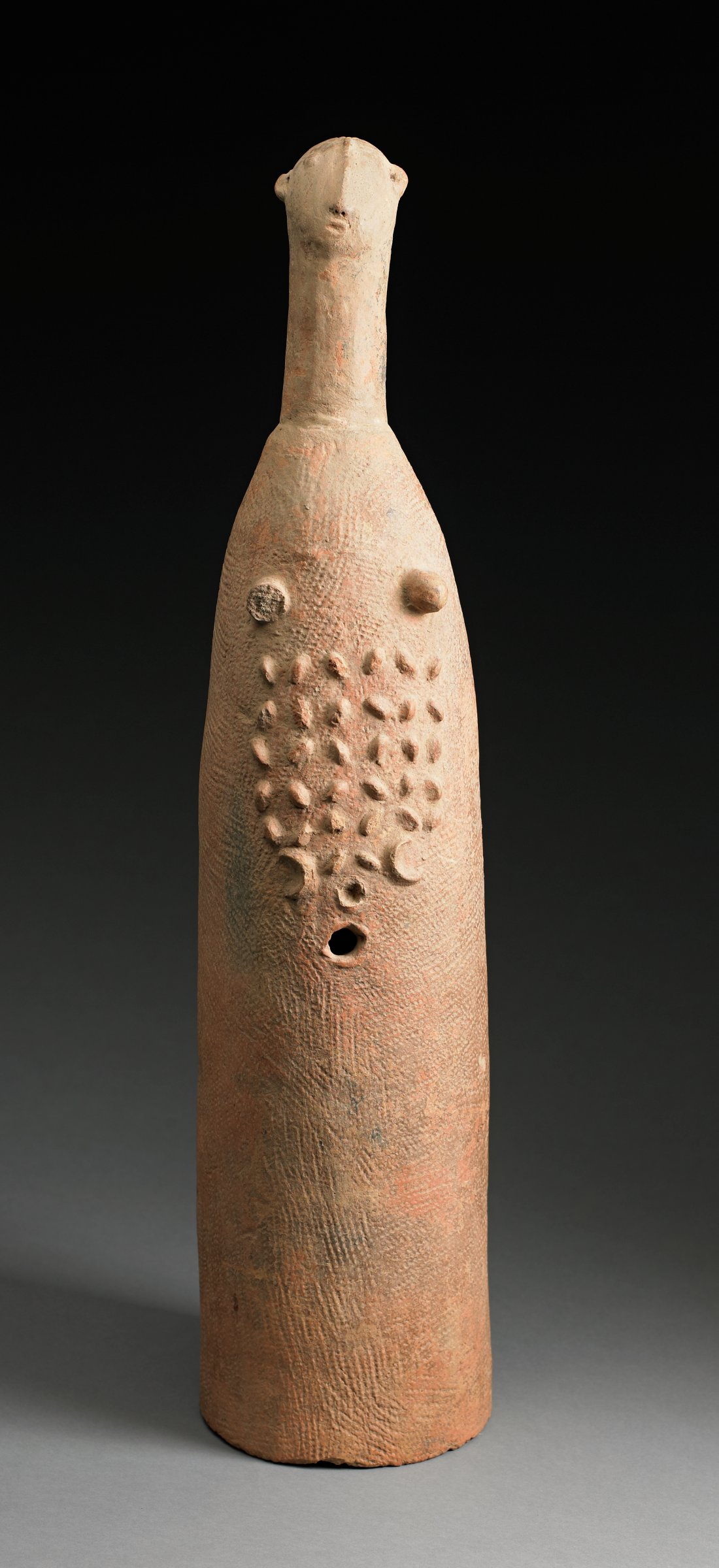 Tall cylindrical figure with long neck and human head has breasts, raised pattern on abdomen, and small round hole below pattern.