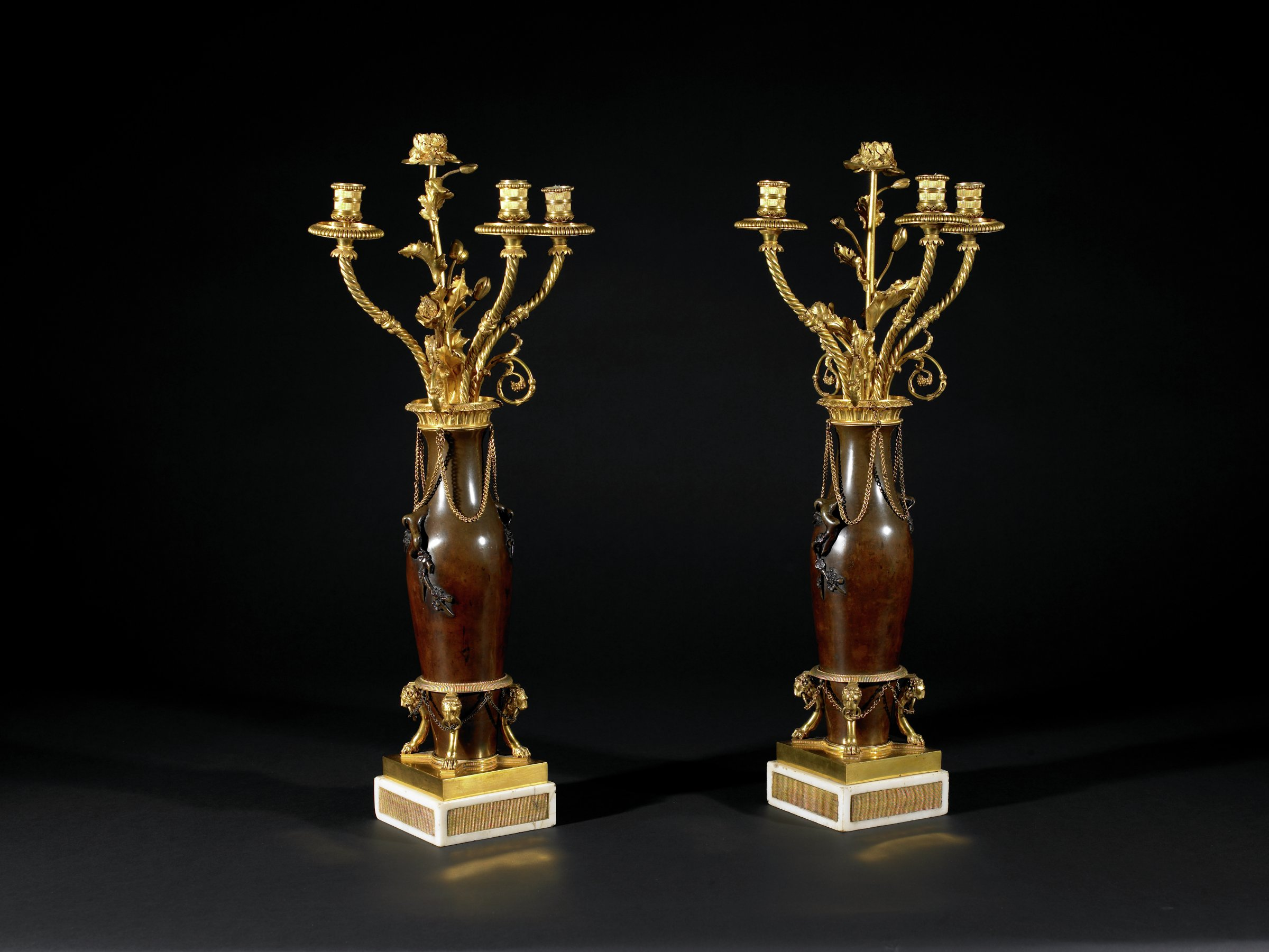 Pair of gilt-bronze and Japanese patinated bronze three-light candelabra, the ovoid patinated bronze vase surmounted by a foliate-molded gilt-bronze top issuing three twist-turned candlearms centered by a scrolling foliate-molded bouquet over draped chains, raised on a stand composed of three monopodial supports headed by lion's heads, and resting on a stepped bronze and white marble plinth.