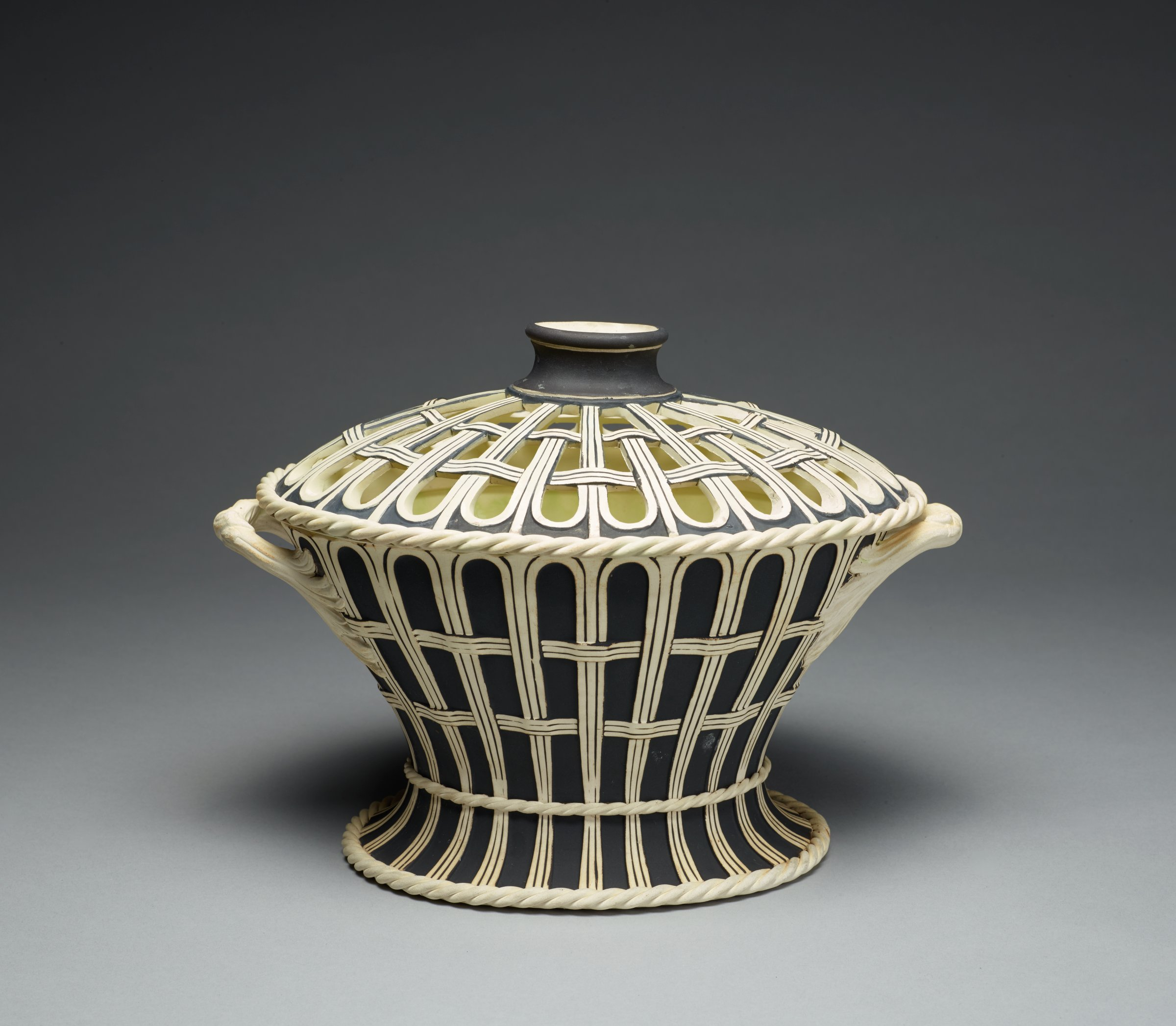Covered bouquetiere, or flower container, of white stoneware covered with a matt black glaze, oval in shape and designed to resemble a footed basket with two looped, twig handles, with a rope twist border at the foot and edge of cover, the pierced, domed corresponding cover with a hole in the middle and short neck, the interior likewise glazed.
