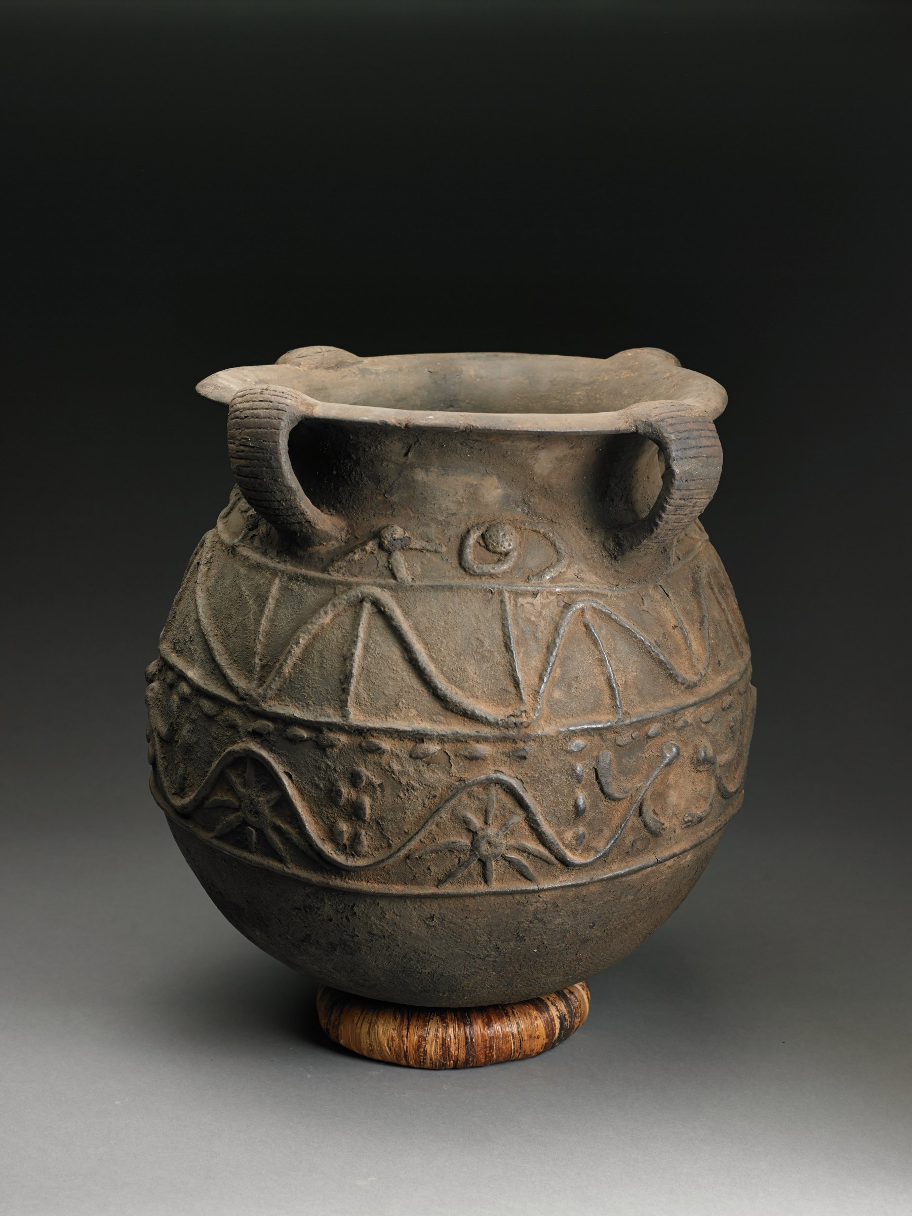 Blackish-brown globular vessel has neck and curved rim; four convex bands connect top of rim back to body of vessel, forming handles. Appliqued serpentine animals interspersed with sunburst or spider forms, raised ovals, and raised vertical lines adorn body of vessel.