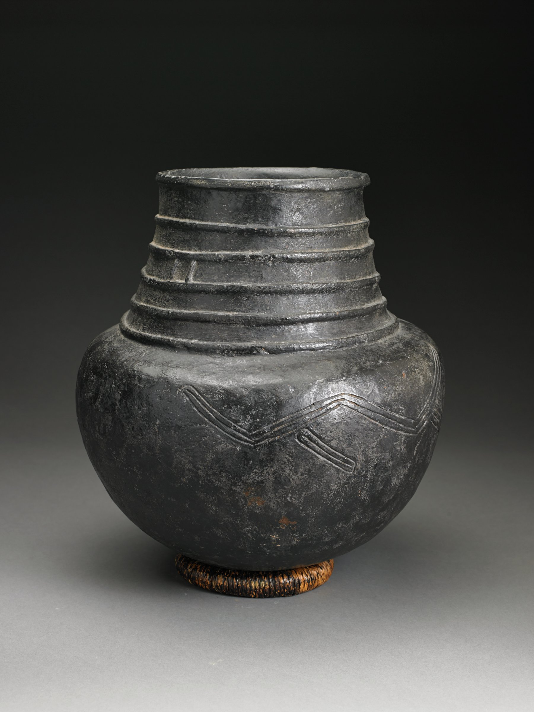 Dark brownish-black vessel has round bottom and narrower neck with parallel raised bands; body has incised horizontal abstract design.
