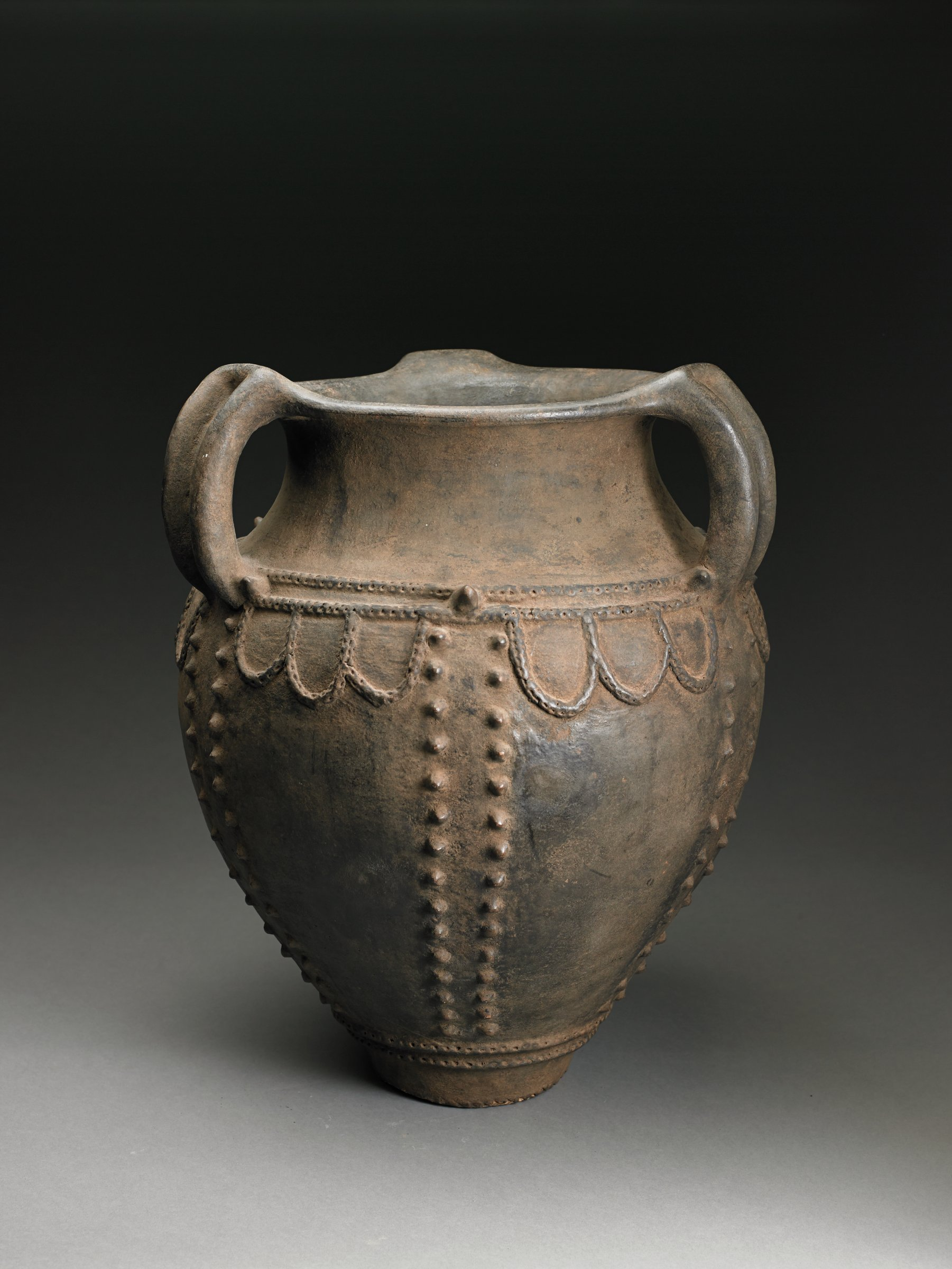 Blackish-brown amphora shaped vessel has narrow bottom and handles. Raised scalloped pattern descends from ridge at shoulder. Double vertical rows of raised dots connect shoulder to bottom of vessel at four places.