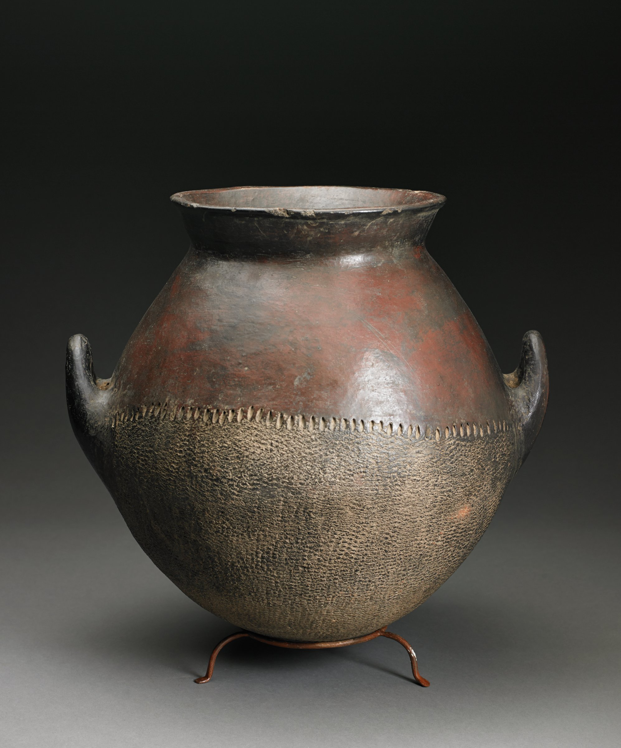 Brown, ovoid vessel narrows at neck and has everted rim and lug handles; bottom half of vessel has overall roulette texture and matte, buff-colored surface and top half of vessel is glossy dark brown.