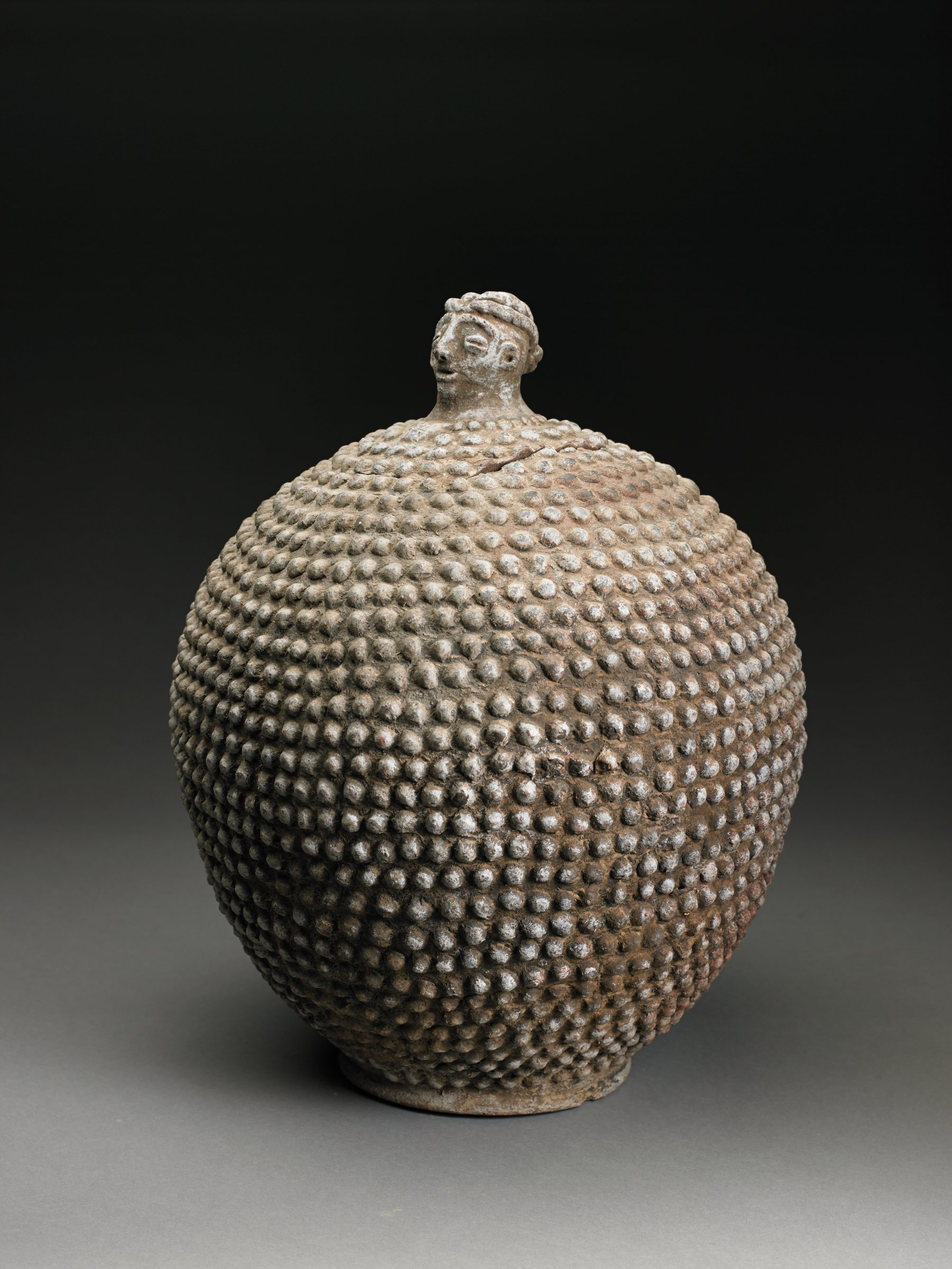 Round, brownish, footed vessel has cut-in lid with knob in form of modeled human head. Entire vessel and lid covered with raised knobs and whitish pigment.