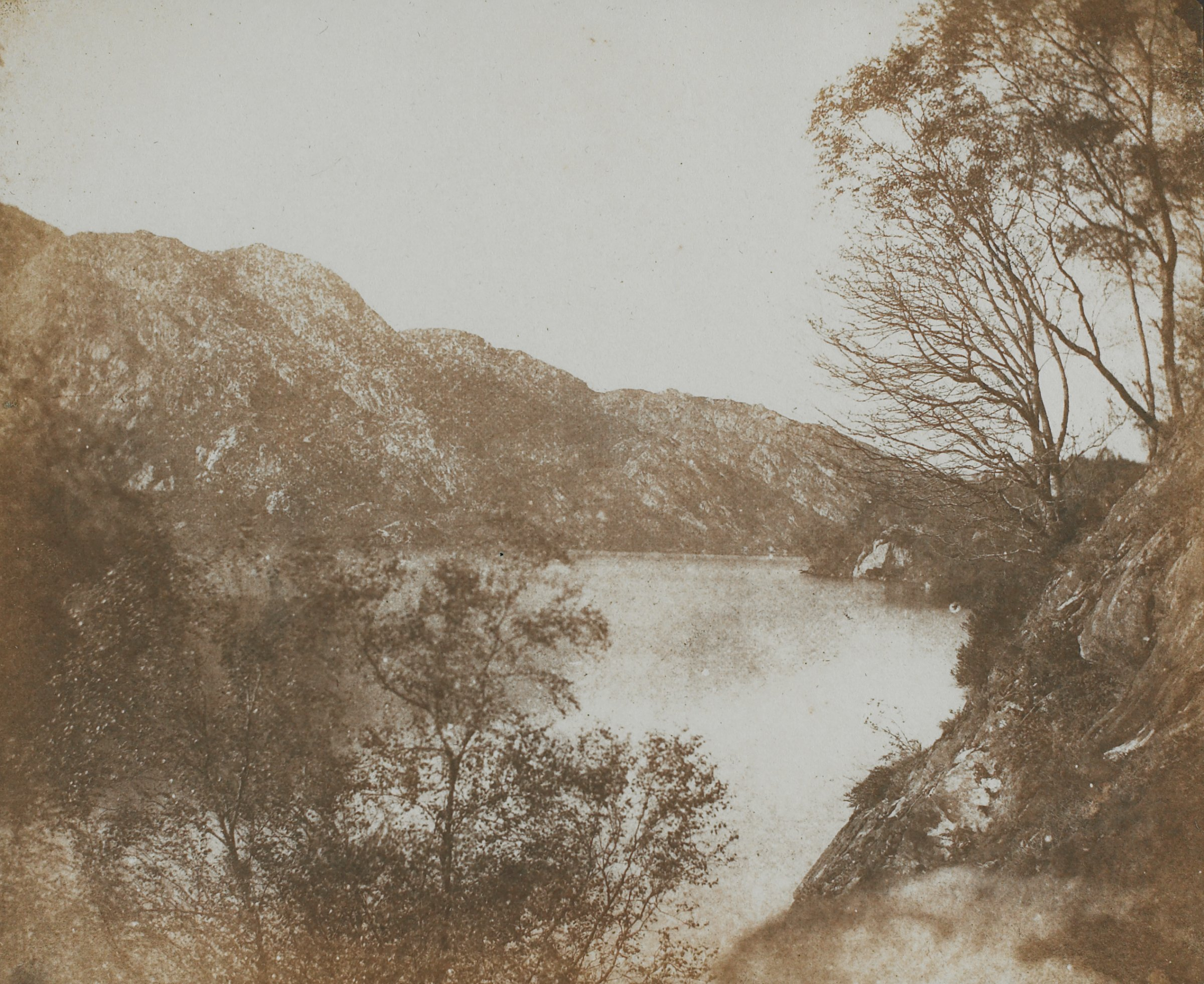 This salt print provides a picturesque view of Loch Katrine, Scotland, looking to the base of Ben Venue with woodland in the foreground.