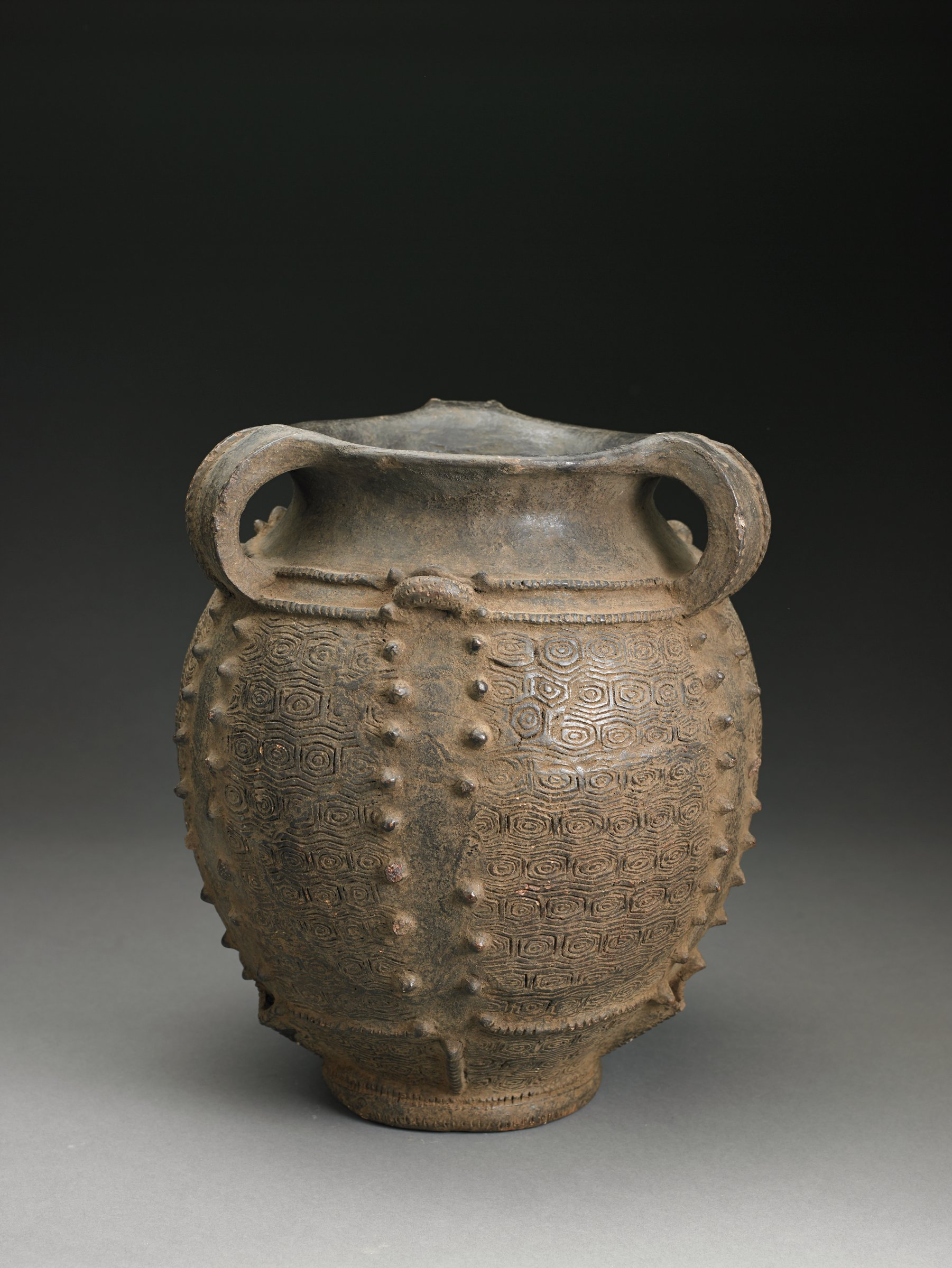 Brown, ovoid vessel has flat bottom, everted rim, and four strap handles. Body of vessel covered with overall incised geometric pattern and parallel vertical rows of raised bumps.