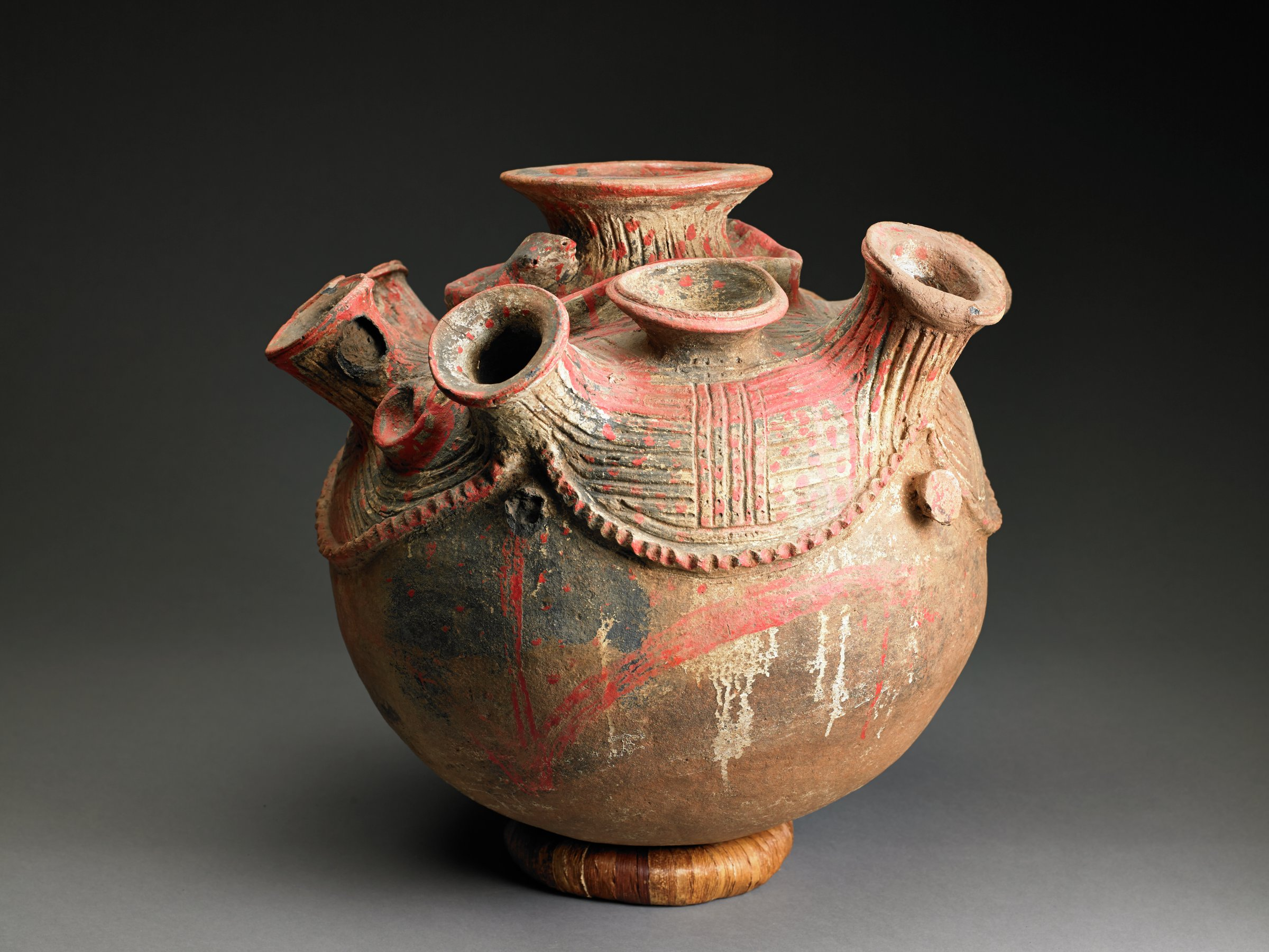 Round, brownish vessel with four knob handles has large spout opening at top, and numerous spout openings around shoulder; appliqued snake figure winds around openings, and red pigment is applied to spouts and snake.