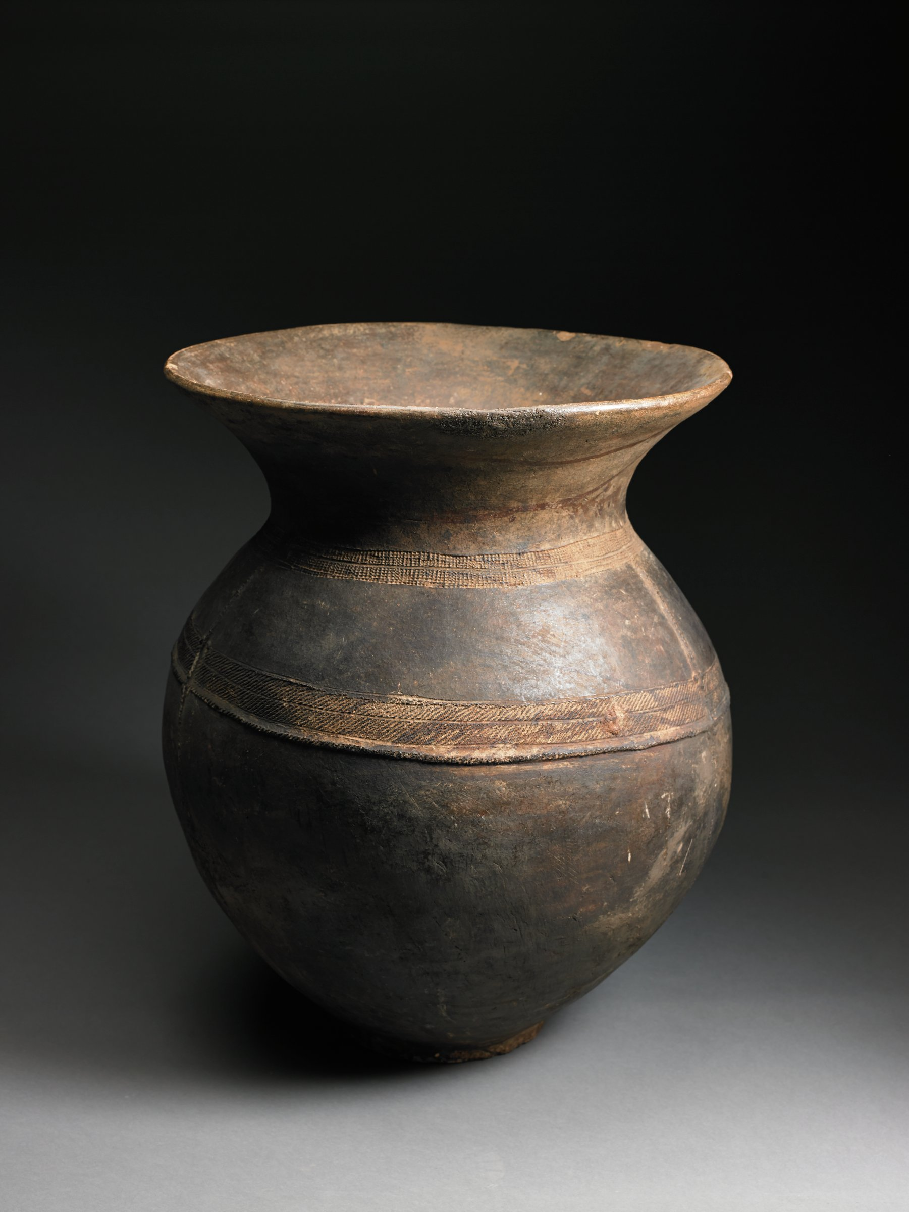 Brown, ovoid vessel indents deeply and tall neck flares outward. Shoulder and mid-section have band of roulette pattern; single vertical line bisects body of vessel with two raised bumps on either side of line.