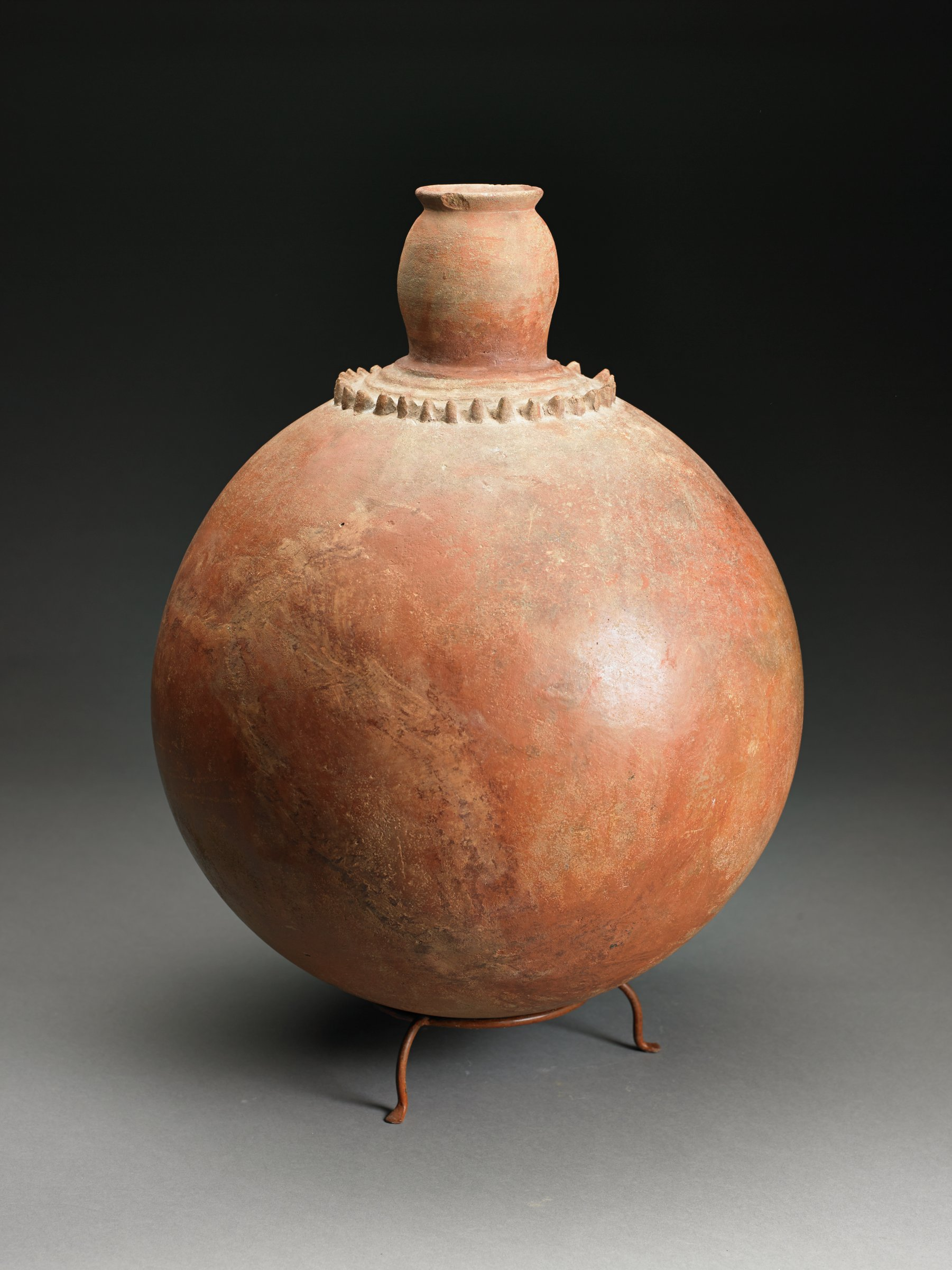 Spherical, brown vessel with black fire clouds has columnar, slightly convex neck with everted rim; shoulder has row of raised spiky points.