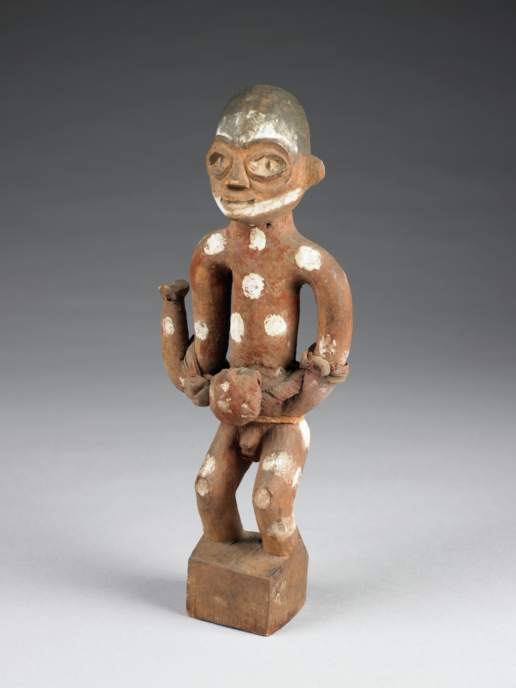 Standing male figure with flexed knees and solid block for feet; one hand on hip, one arm raised with elbow bent (hand broken off). Heart-shaped face with thick rims around eyes. Packets of medicinal material wrapped in fabric on abdomen and elbows. Surface colored with base of reddish-brown pigment; large white spots of pigment on body and white marks on face
