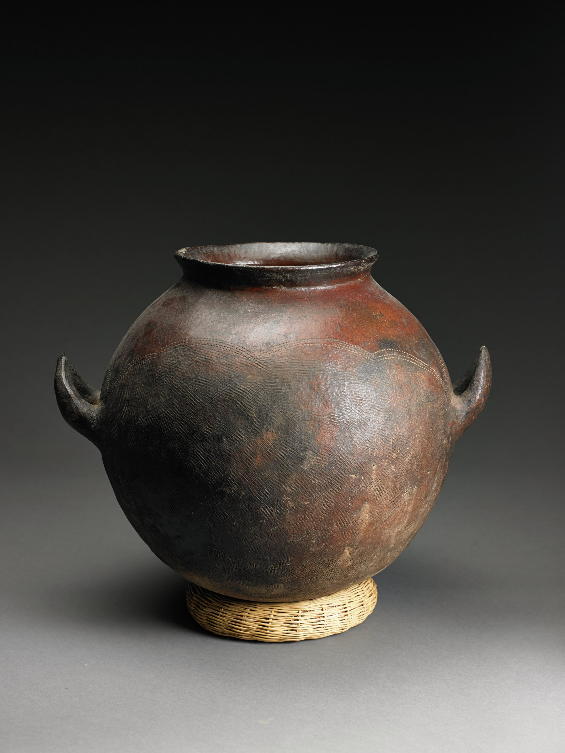 Dark-brown, spherical vessel has lug handles on the sides and short, vertical neck; shoulder has incised arcs with overall roulette pattern below.